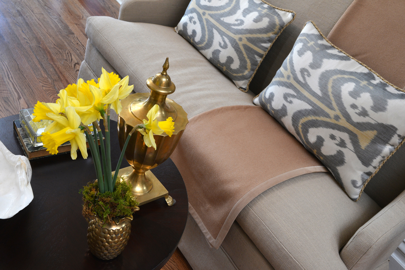 Decorative accent pieces and flowers atop an occasional table paired with settee | Savage Interior Design