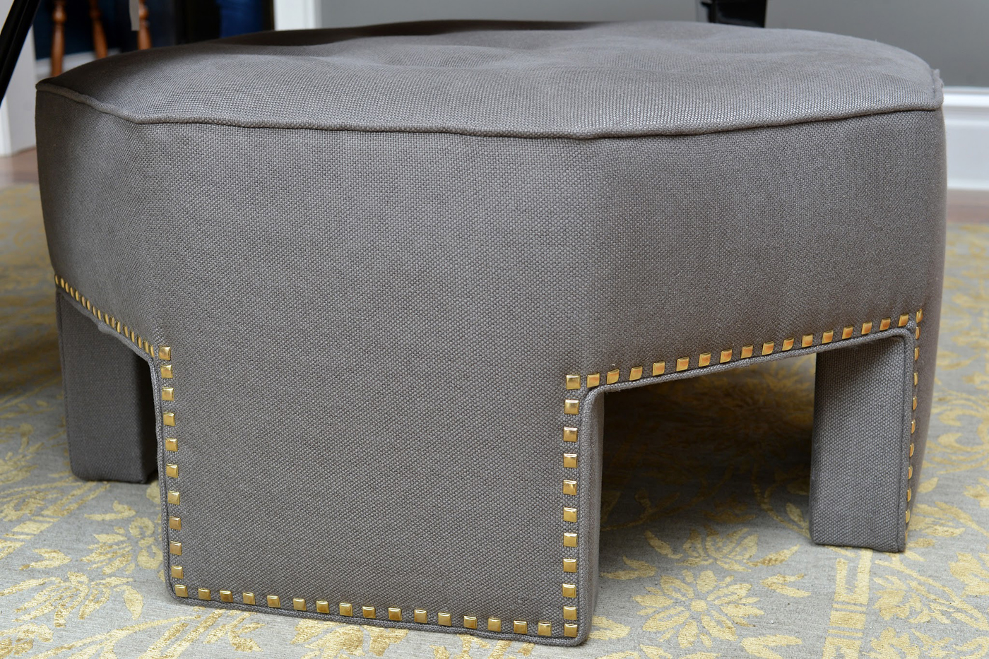 Clean-lined detail of upholstered gray ottoman with square brass nails / studs | Savage Interior Design