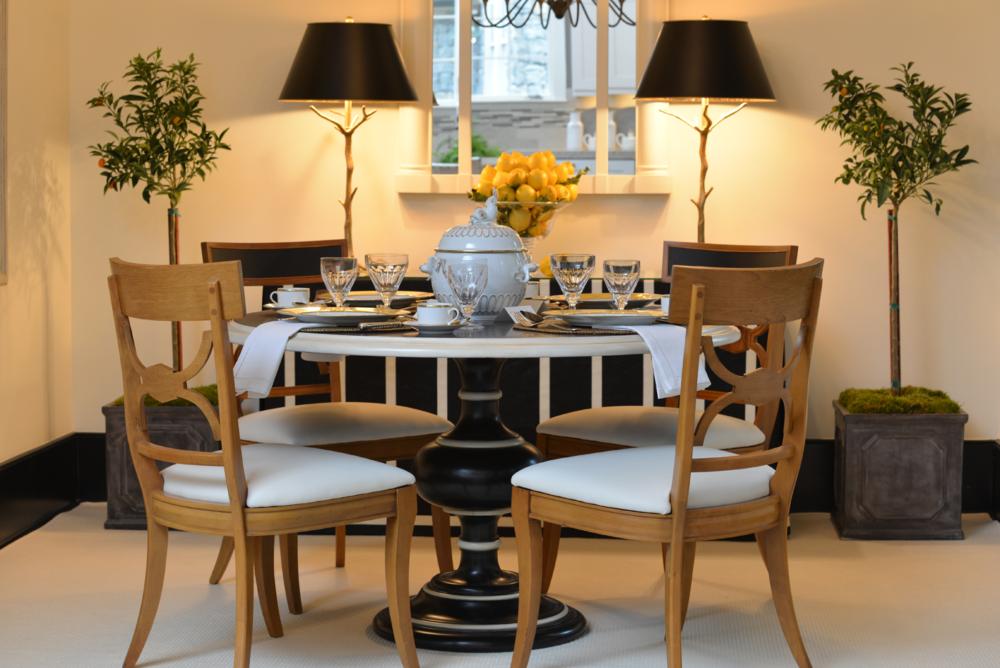 Black and white pedestal dining table with blonde Biedermeier style chairs | Savage Interior Design