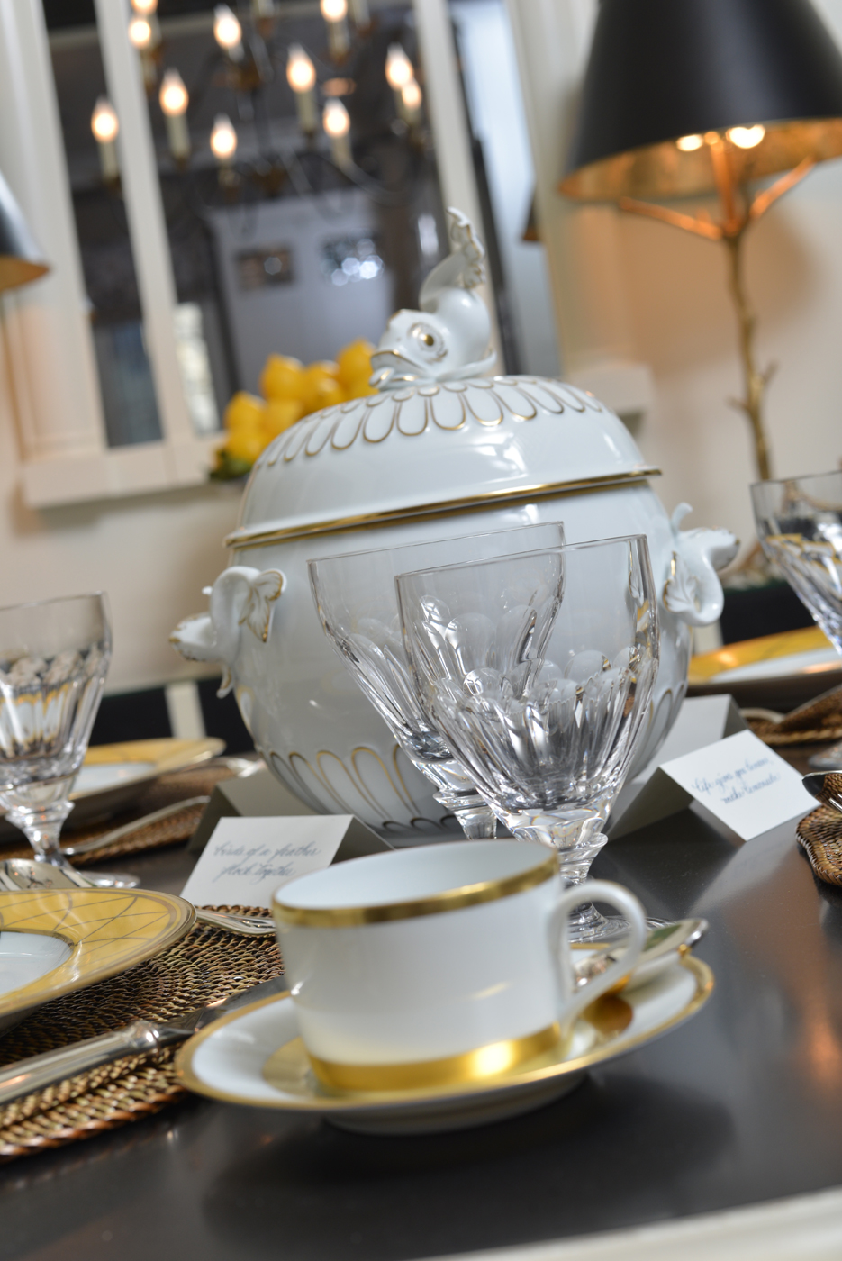 White porcelain tureen trimmed in gold with dolphin finial surrounded by crystal glassware | Savage Interior Design