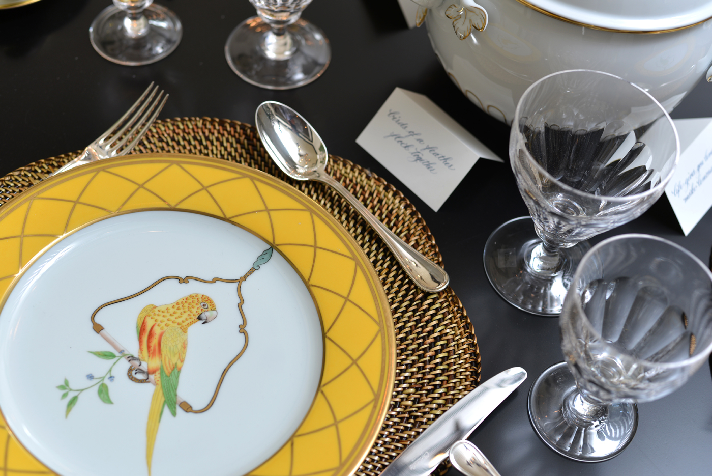Place setting with yellow, green, and red parrot on white china plate with yellow rim trimmed in gold | Savage Interior Design