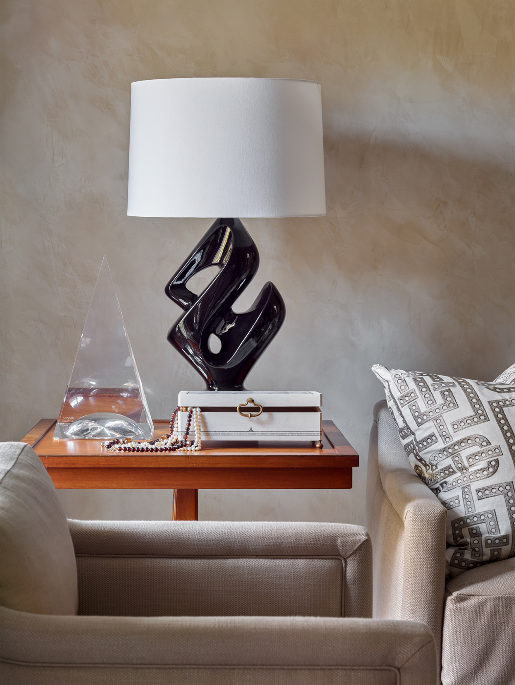 Modern black lamp, obelisk, and jewelry box on side table;  armchair covered in linen | Savage Interior Design