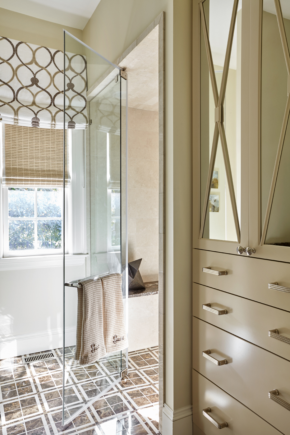 Bathroom cabinetry with mirrored doors; shower enclosure with Emperador Dark and Crema Marfil marble | Savage Interior Design