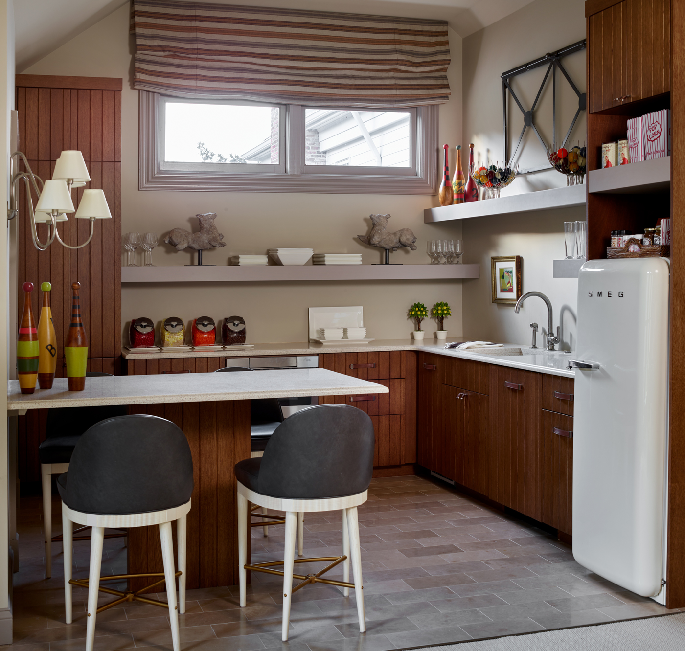 Modern kitchen with medium stained wood finish, counter stools, and retro Smeg refrigerator | Savage Interior Design