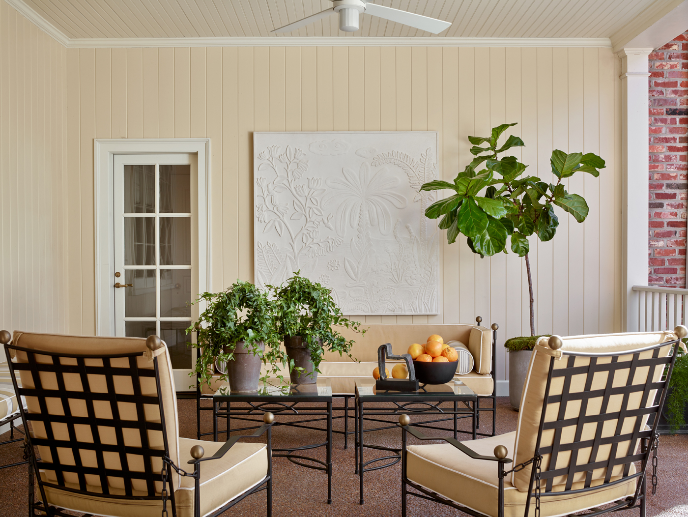Outdoor covered patio with iron chairs, occasional tables, and settee; chairs have exposed latticework grid back | Savage Interior Design