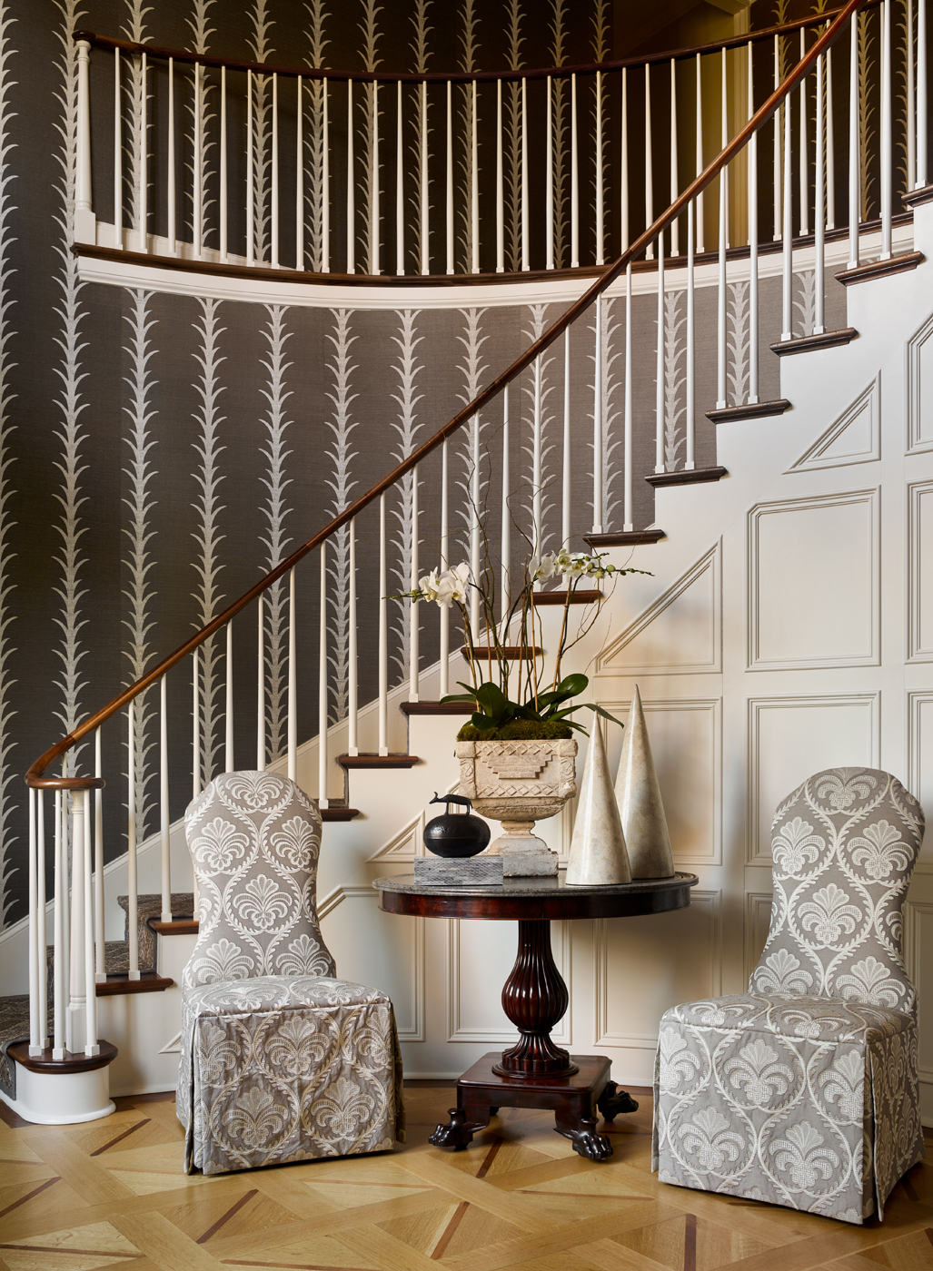 Entryway and curved staircase with Schumacher Acanthus Stripe wallpaper & parquet wood floors | Savage Interior Design