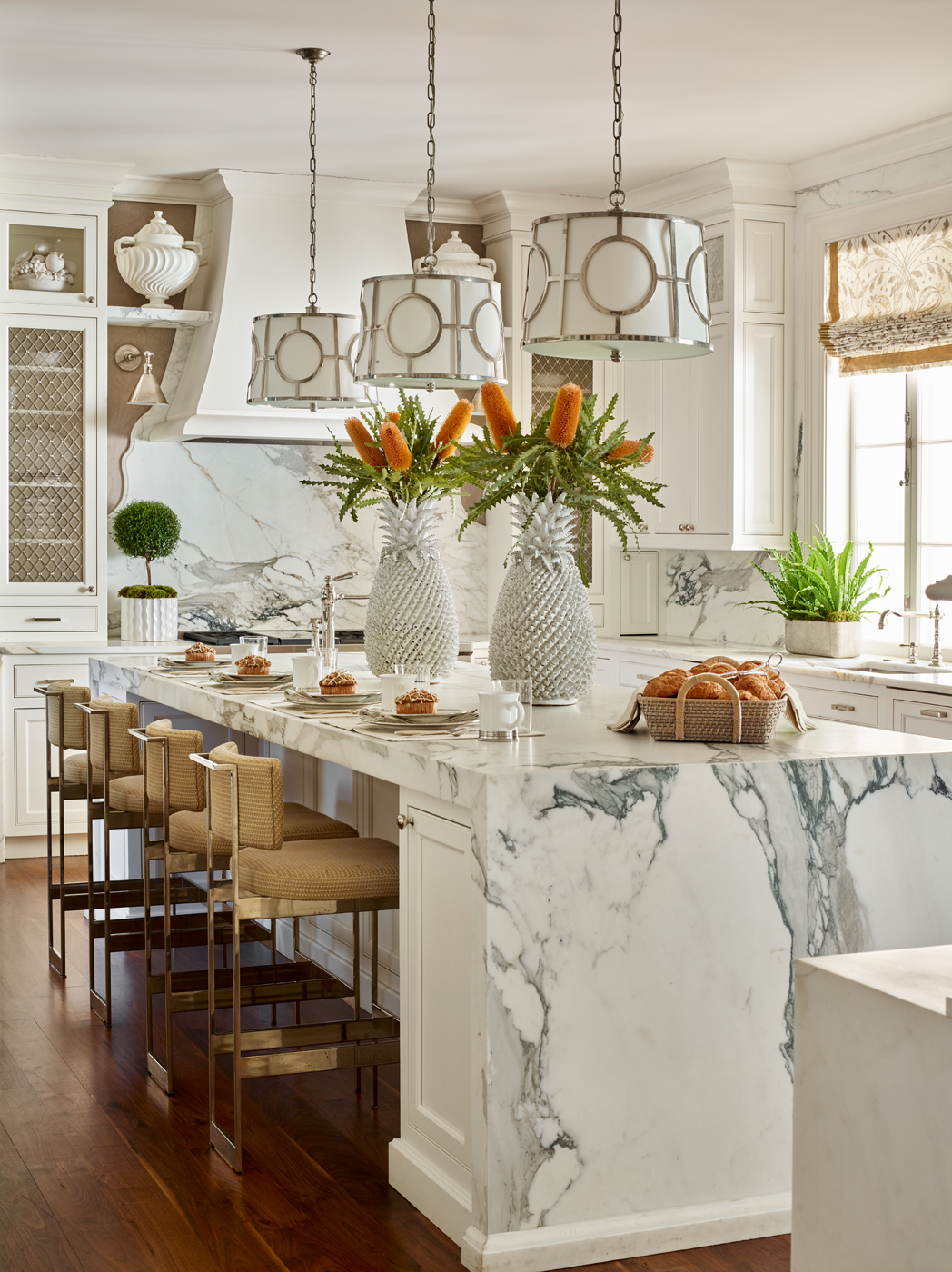 Custom white kitchen with Calacatta Borghini marble slabs and woven leather stools by Powell & Bonnell | Savage Interior Design