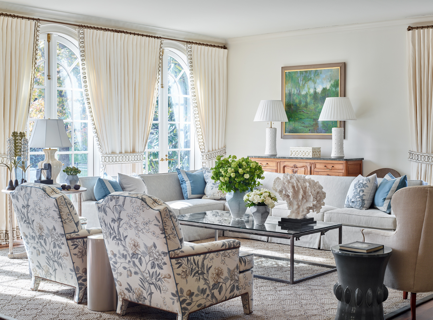GP & J Baker floral fabric on tight-back arm chairs in family room; linen window treatments & French doors | Savage Interior Design