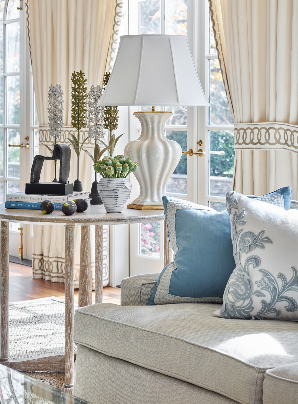Family room vignette with cerused wood end table & white ceramic lamp; linen window treatments | Savage Interior Design