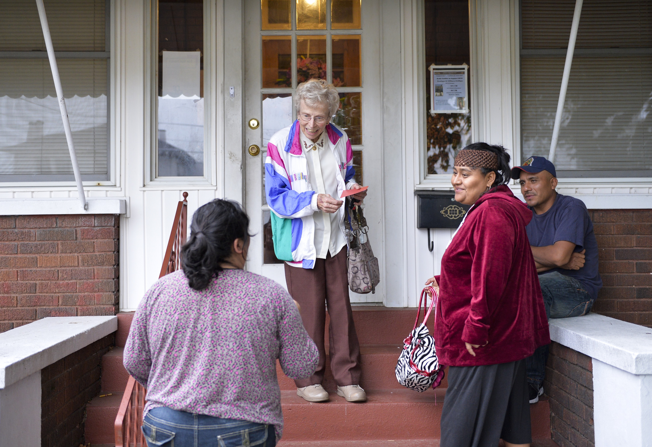 Sister Fran Wilhelm takes a moment before evening Mass to chat with Maria Reyes (left) and Eutimia and Leoule Carrillo (right) on her front porch at the Centro Latino in Owensboro. Maria, who speaks limited English, had come for help filling out paperwork to apply for food stamps.