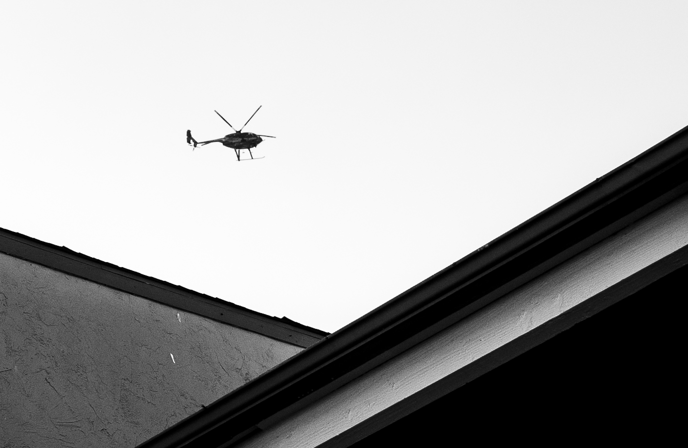 A police helicopter circles over an apartment complex, searching for suspects after a drug related shooting.