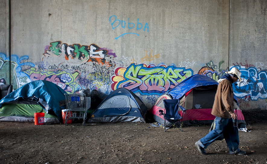 "Clark ""Wayne"" walks by a row of tents he and other homeless residents of Columbus, Ohio set up beneath a bridge on the west side. As parts of the city are renovated many homeless residents are pushed to the edges of Columbus."