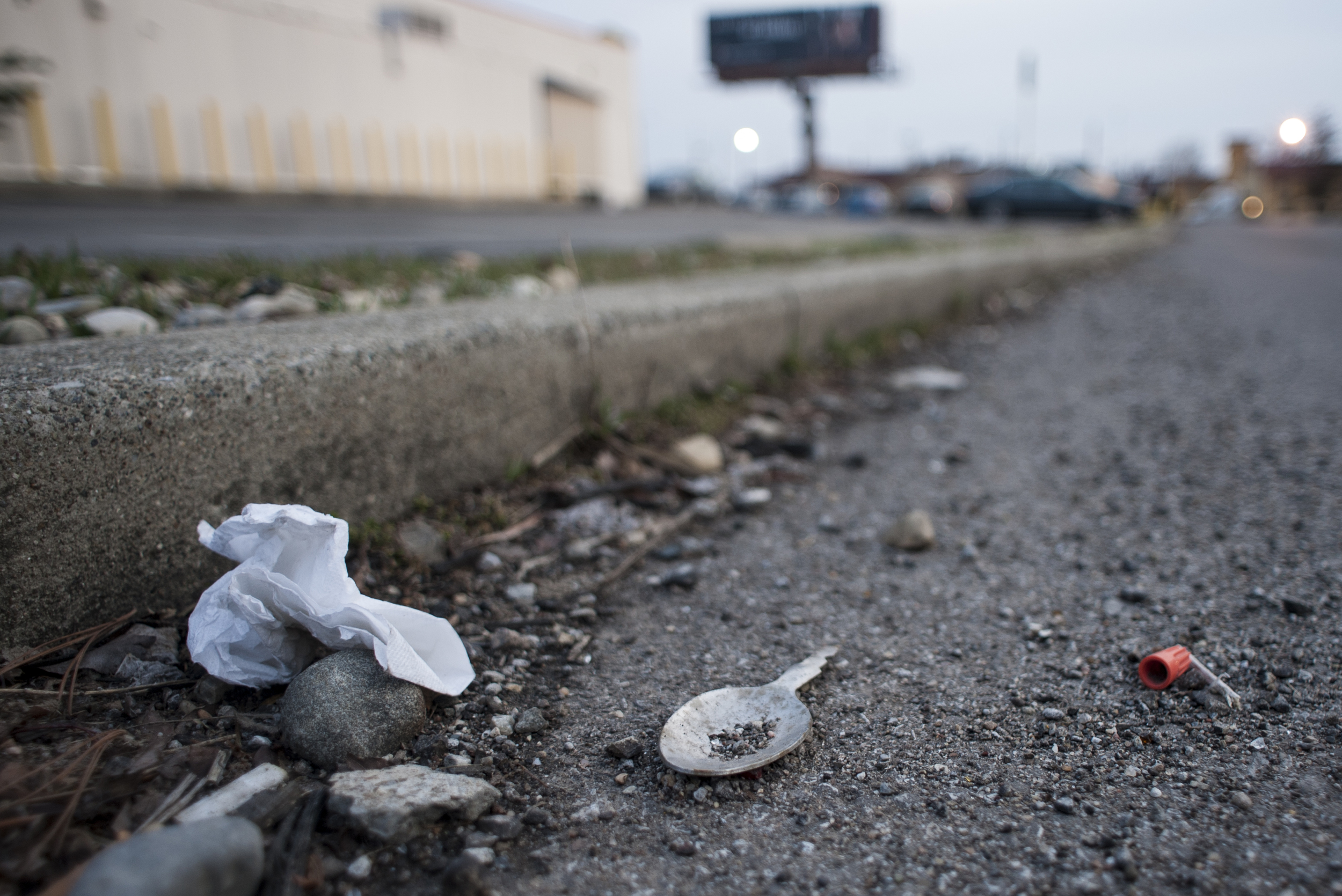 A spoon that was most likely used to prepare a dose of heroin lies next to a syringe cap in a parking lot.