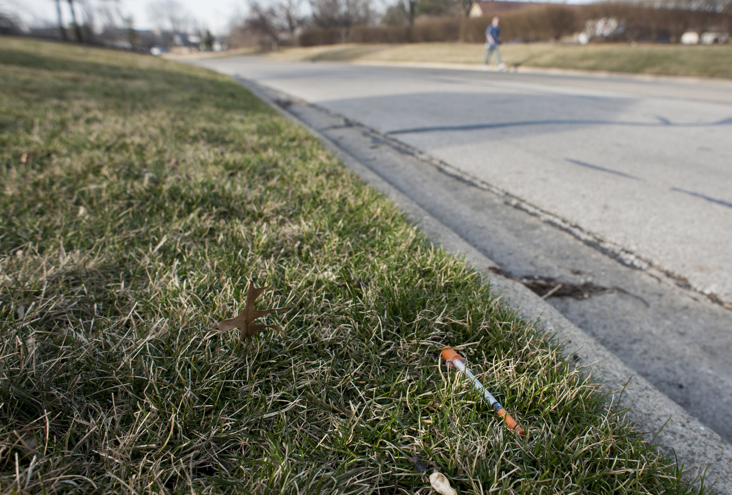 Another needle lies discarded on the side of the road in a suburb. Used needles pose a public health risk to those uninvolved with the use and sale of drugs, inlcuding children and pets.