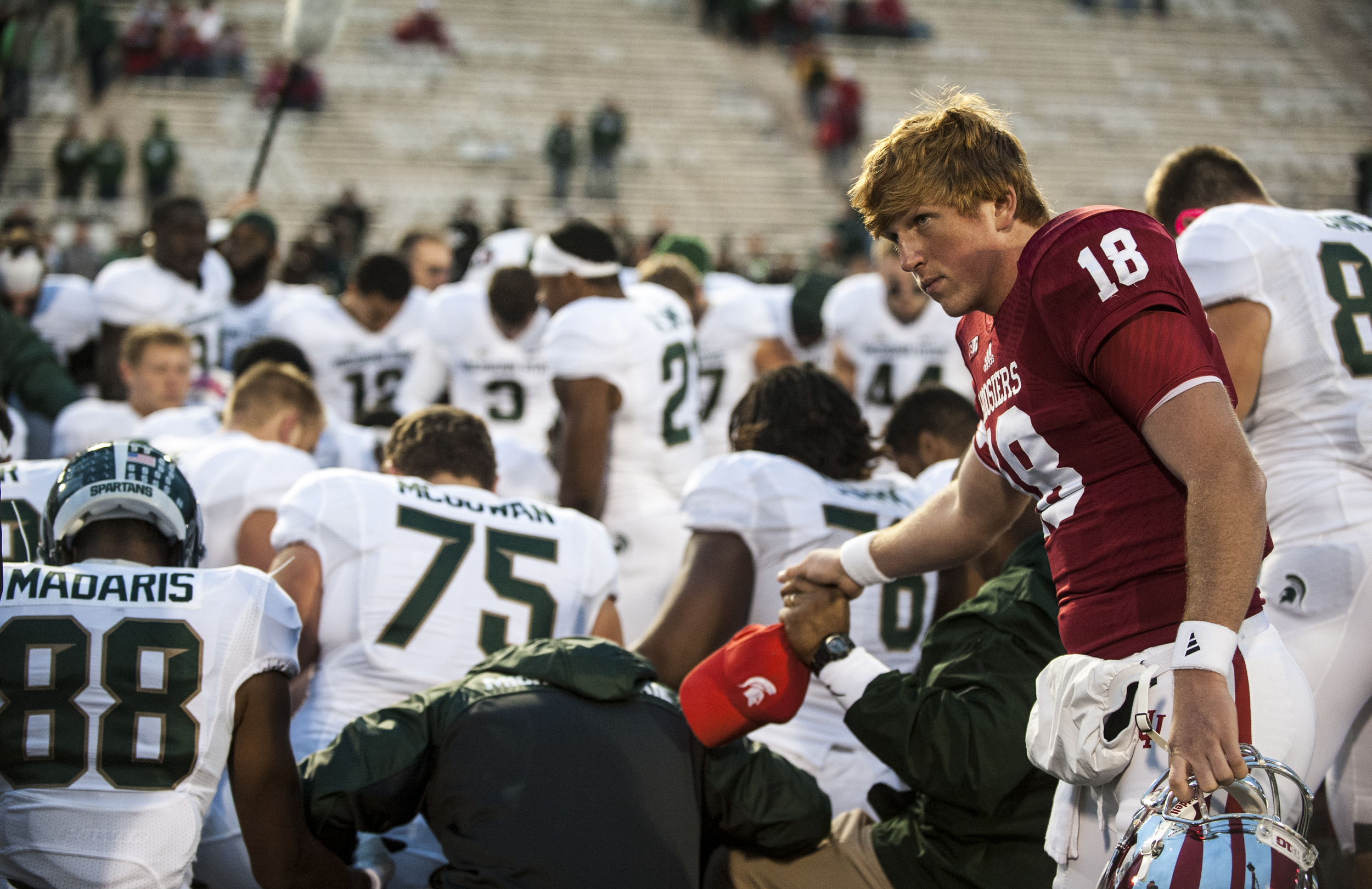 After a devastating 17-56 defeat at their own homecoming against Michigan State, Hoosiers quarter back Danny Cameron joins Michigan State players in a post game prayer on Saturday, October 18.