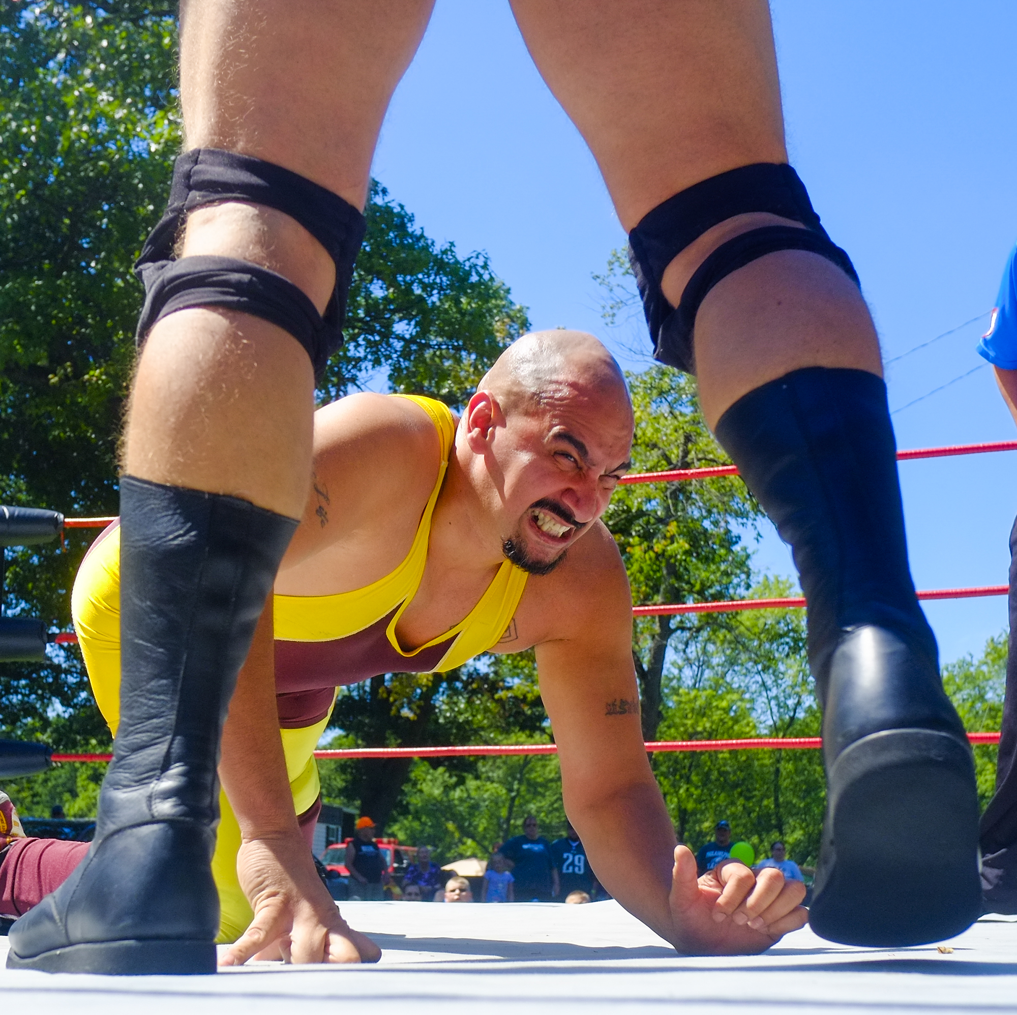 A wrestler grimaces as his opponent approaches him in the ring during a wrestling expo at the Marion Party in the Park festival.