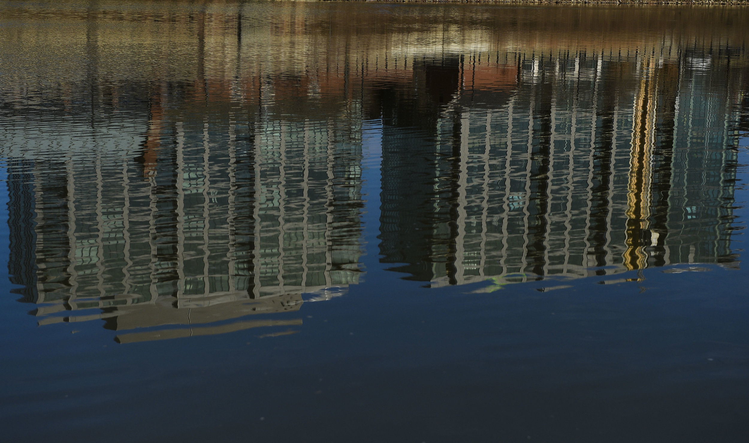 Newly built high rise apartments are reflected in the waters of the Scioto near Confluence Park in Downtown Columbus, Ohio.