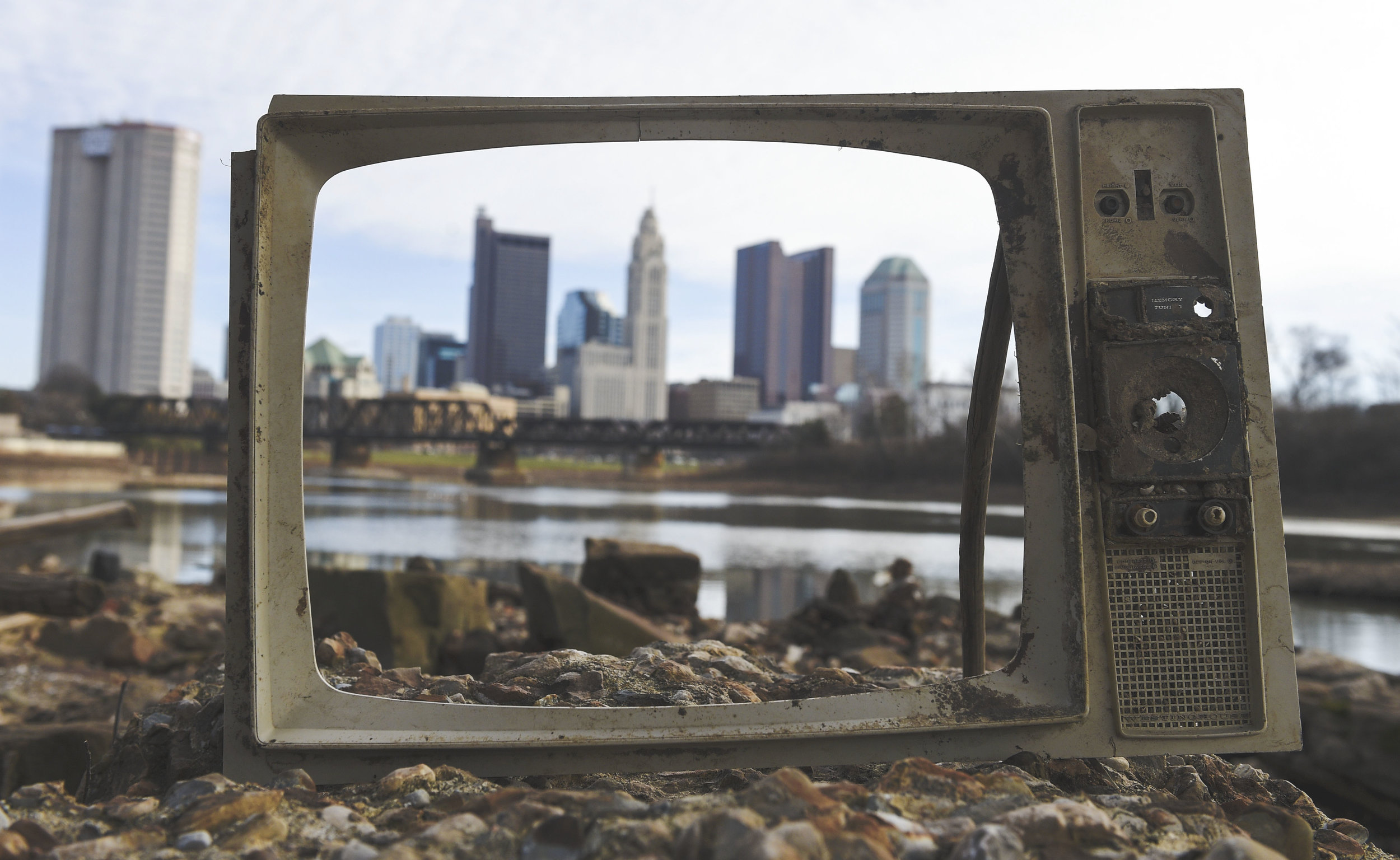 The downtown area of Columbus as seen through the remains of an old Television that was propped up on a rock on the eastern shore of the Scioto River.