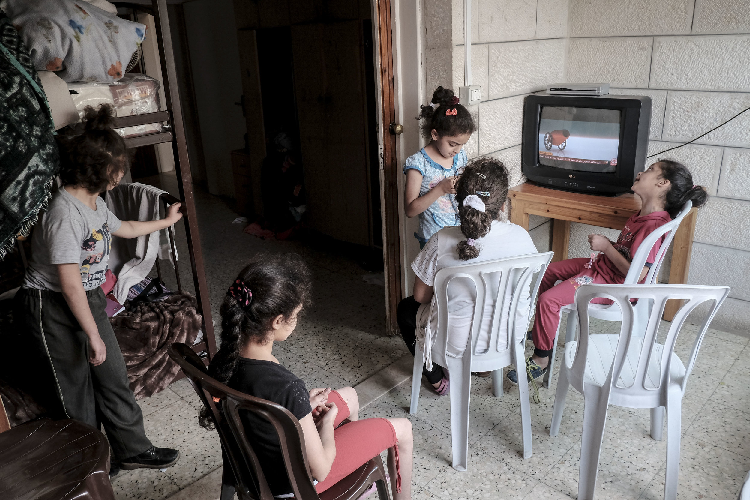 Students of the Peace Center for the Blind sing along to a television program at the Center's boarding house. Many of the students are from the West Bank, and during the schooling year live at the boarding house in East Jerusalem. Living together teaches the students social skills and self care, important skills that many are lacking when they first arrive.