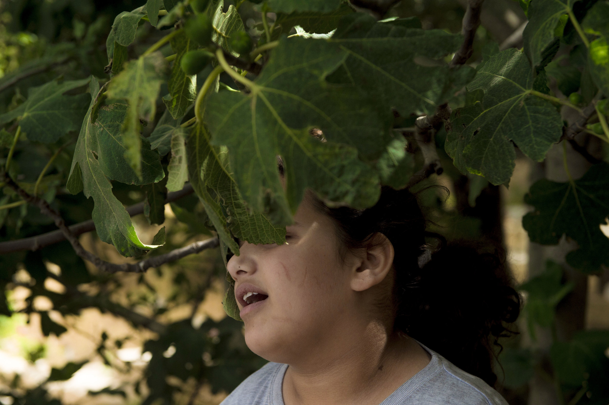 Amira reacts to leaves touching her face during recess at the Peace Center for the Blind in East Jerusalem. Many of the students are not completely blind however have severe limitations with their vision. The students rely on other stimuli such as sound and touch to understand the world and their surroundings.