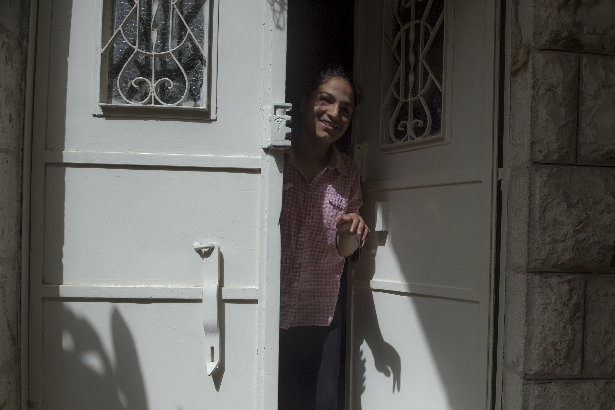 "Fourteen-year-old Muna Taher exits the Peace Center for the Blind for recess during the week of exams. ""When Muna first came to the school she was very much a troubled child, now she is a model student and is excelling in her studies."" One of the teachers at the school comments."