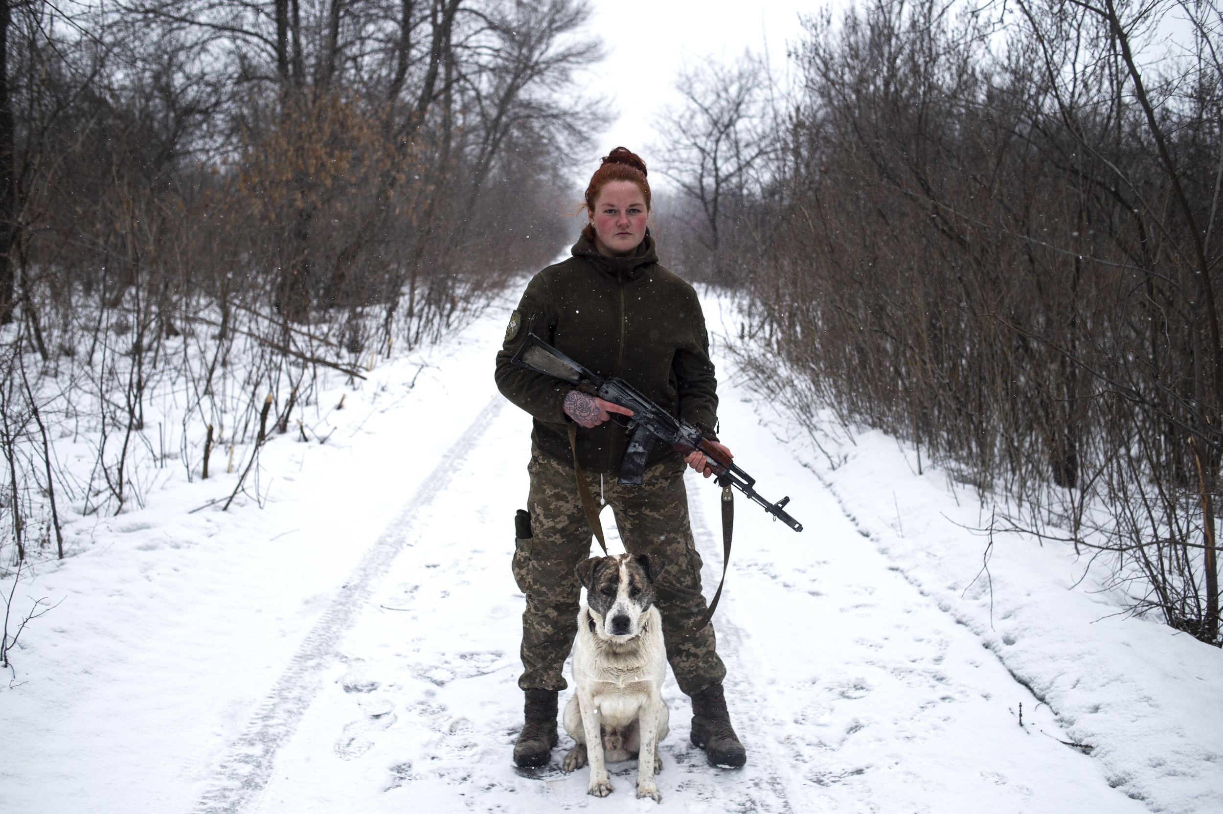Katya, a soldier in the 54th Mechanized Rifle Brigade poses for a portrait with a dog that her platoon has adopted as their mascot, Ser'Oga.