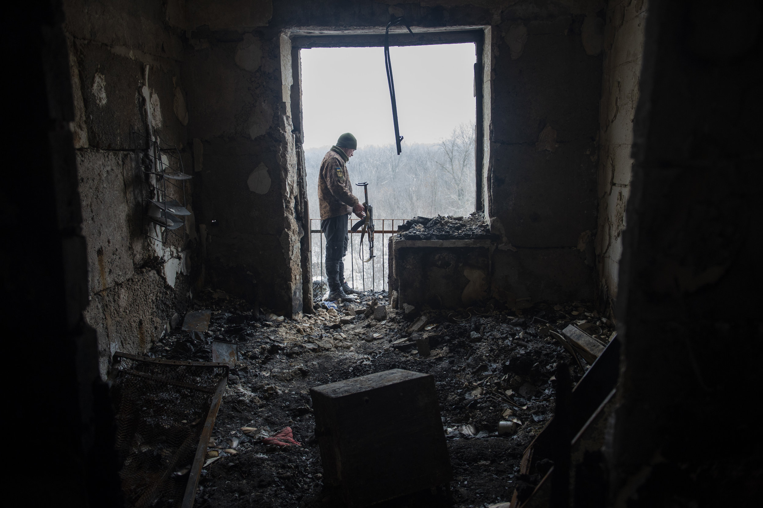 A soldier from the 54th Mechanized Rifle Brigade inspects the results of heavy shelling from the previous night. The building that the soldiers live in is shared also with civilians in Zolote.