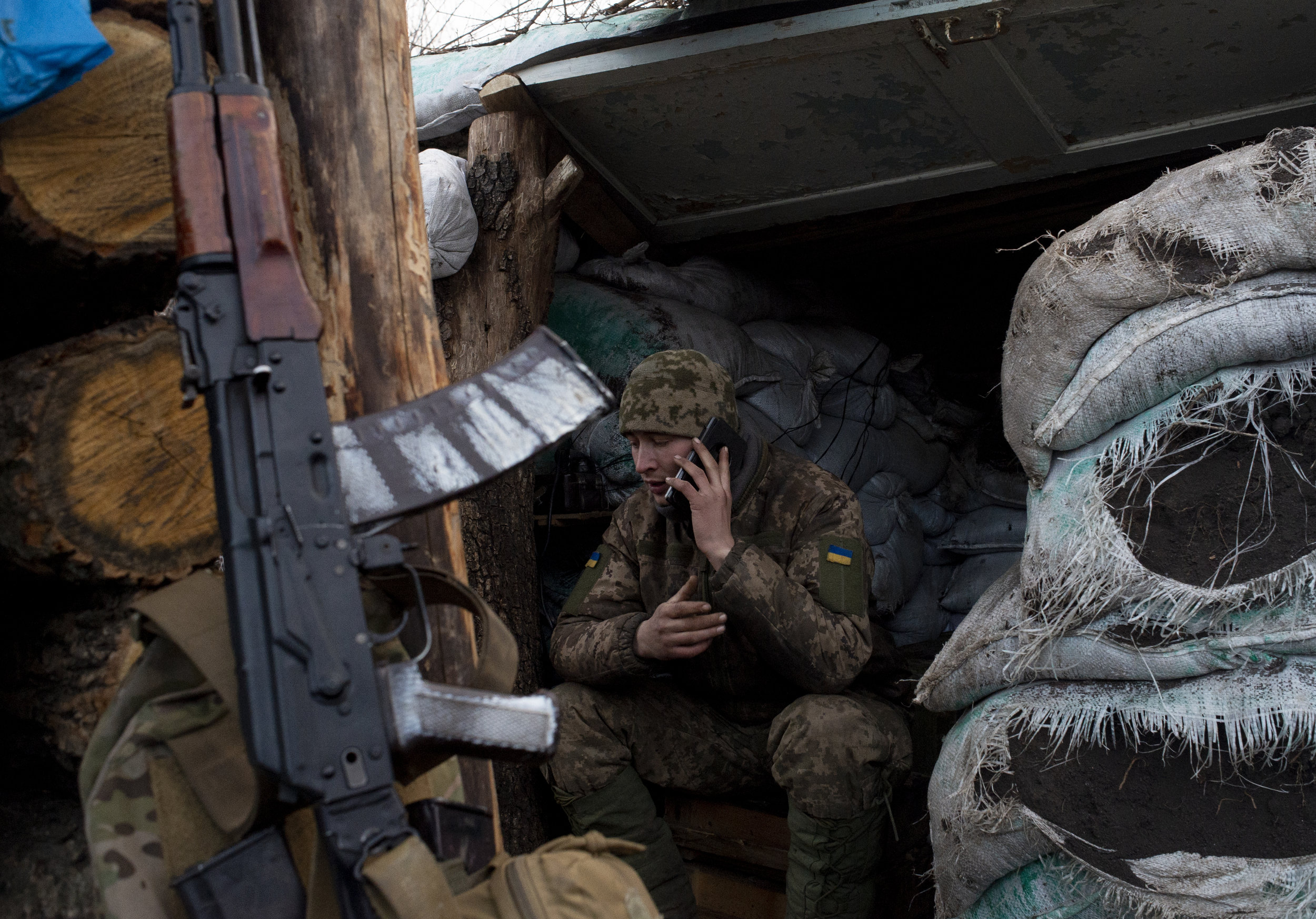 Alexy, a corporal in the 54th Mechanized Rifle Brigade, speaks to his wife on the phone while on duty at Point Zero in Zolote. The Donbas War is marked by the now stagnant line of contact where snipers and artillery reign supreme over troop movement.
