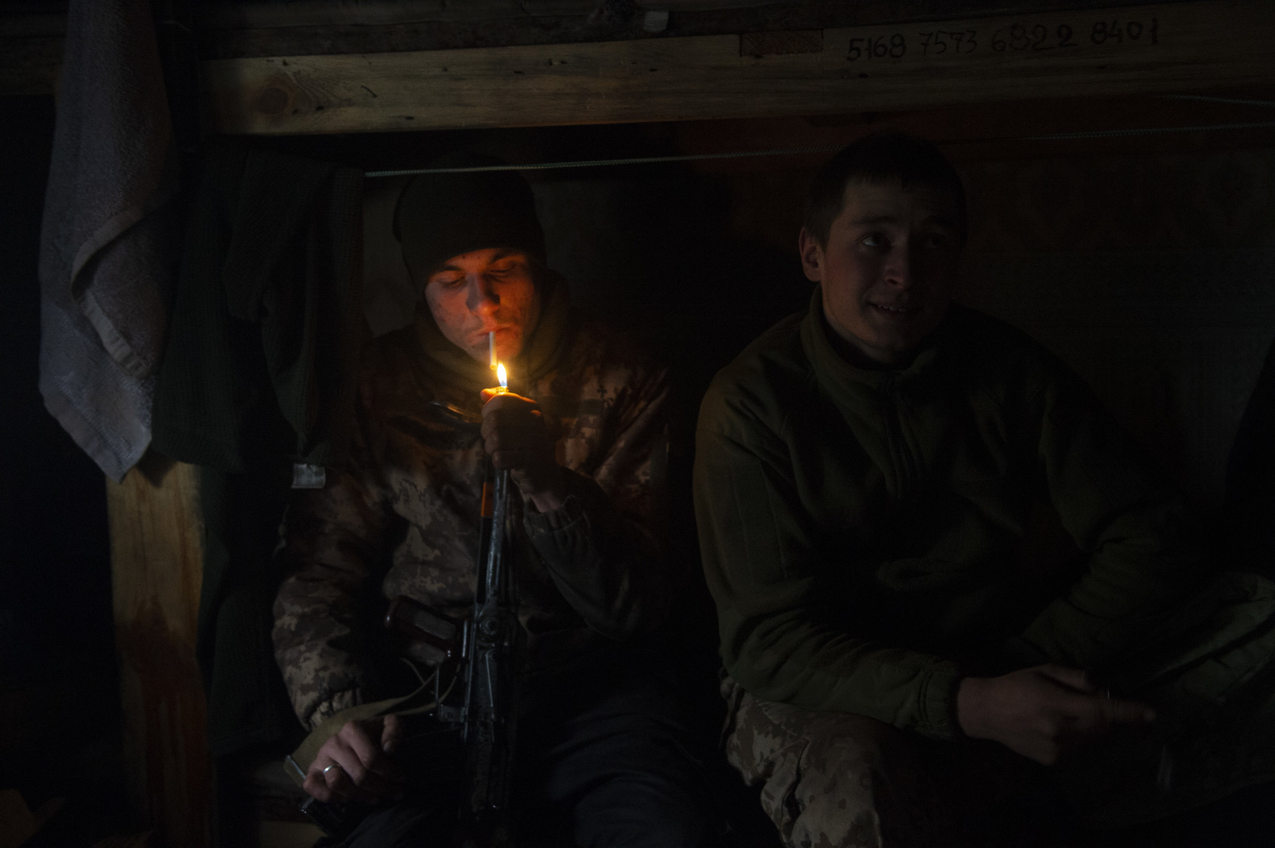 Soldiers pass the time at the front on guard duty, smoking, and sleeping in their makeshift barracks. In Zolote the position come under shelling every night and almost every morning.