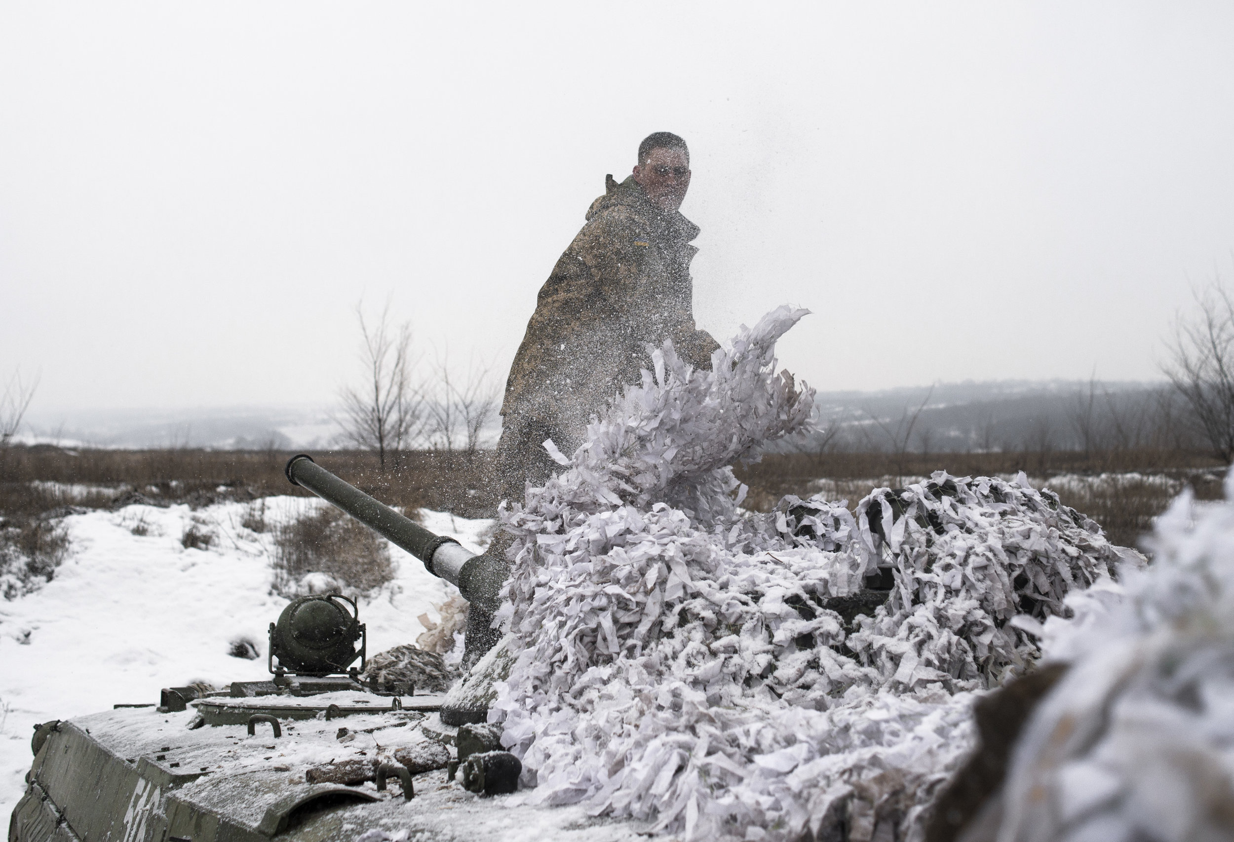 A soldier in the 54th Mechanized Rifle Brigade uncovers an APC or Armored Personnel Carrier that sits ready for fighting on the frontlines of the Donbas War.