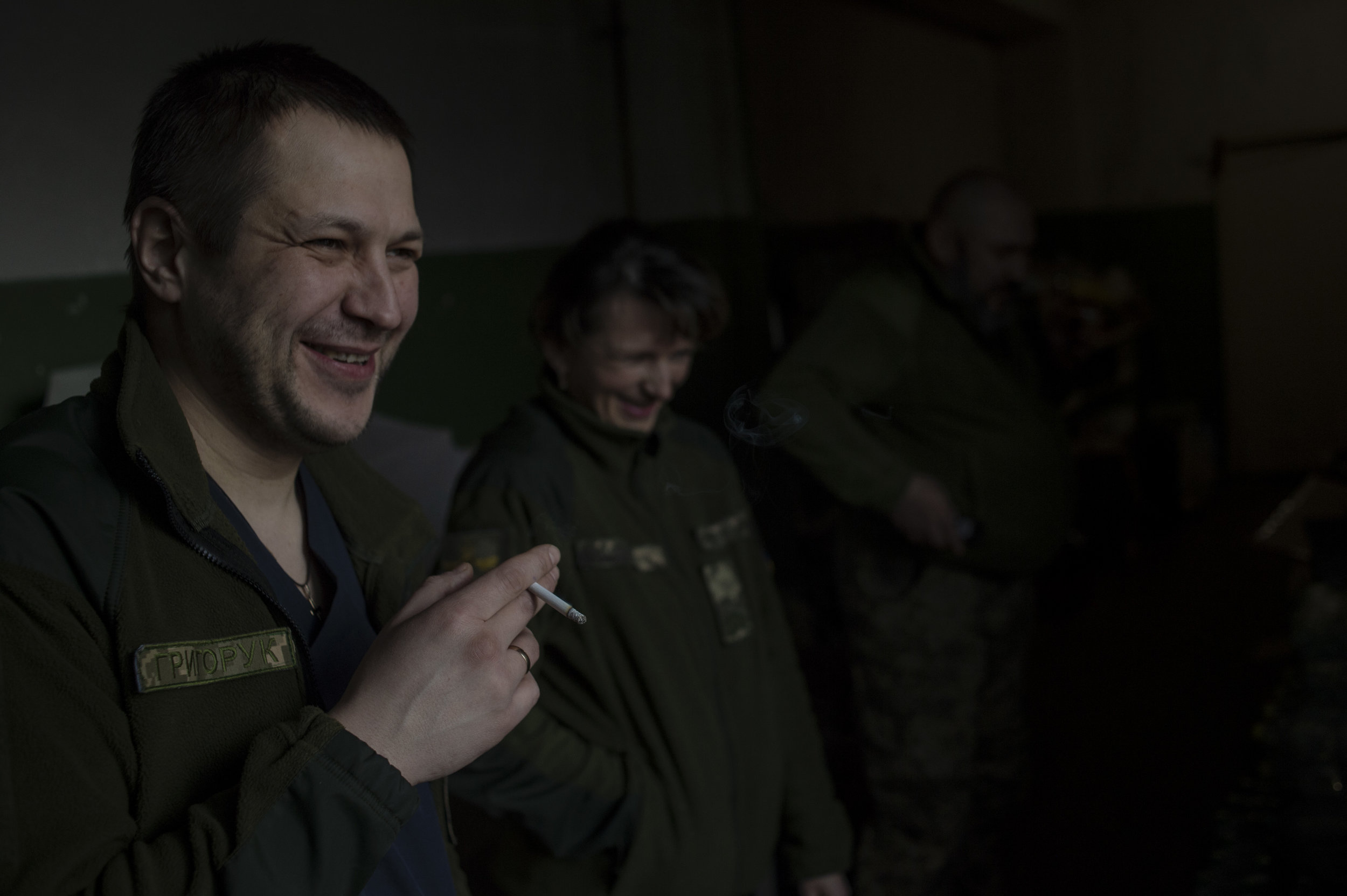Ukrainian military surgeosn and doctors enjoy a smoke break while on shift at a hospital in Zolote. The hospitals that the military uses are shared with civilian doctors.