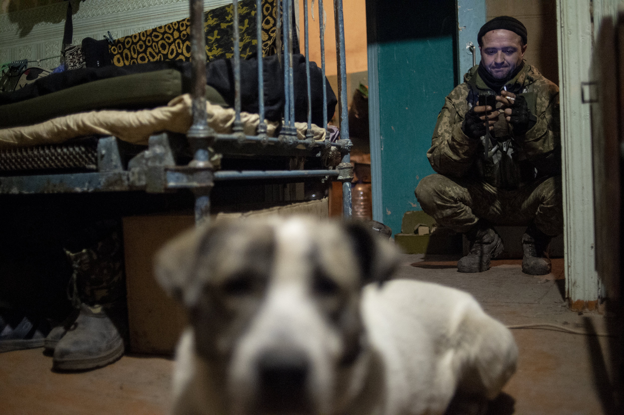 Demitry, a soldier in the 54th Mechanized Rifle Brigade, checks his phone in the makeshift barracks in Zolote shortly before taking his shift for guard duty at point zero.