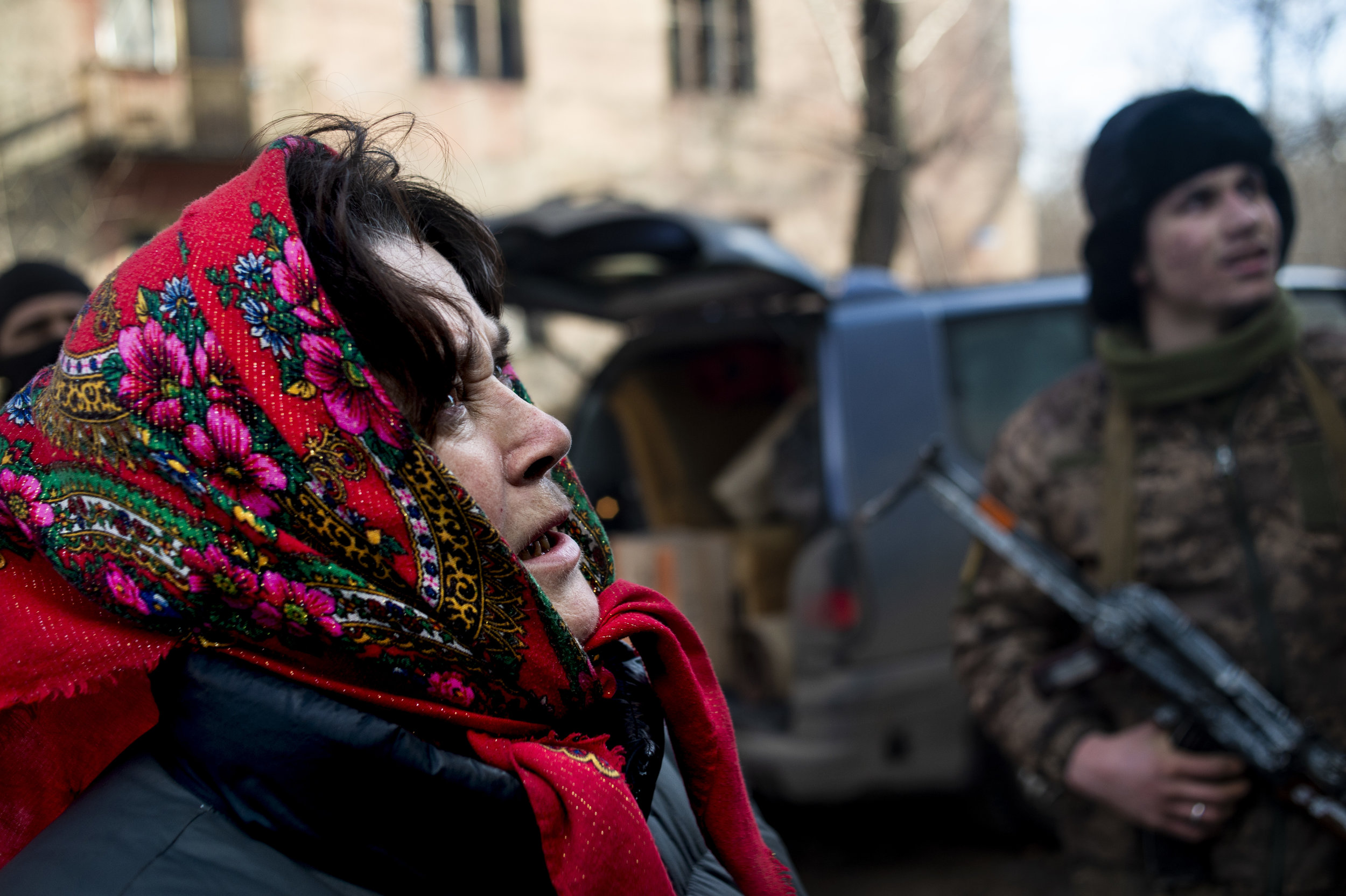 A woman who lived in the apartment building where soldiers of the Ukrainian military lived keeps careful watch as her belongings are loaded into the back of a flatbed truck. Following several days of heavy shelling on the building, several civilians decided to move several kilometers away from Point Zero.