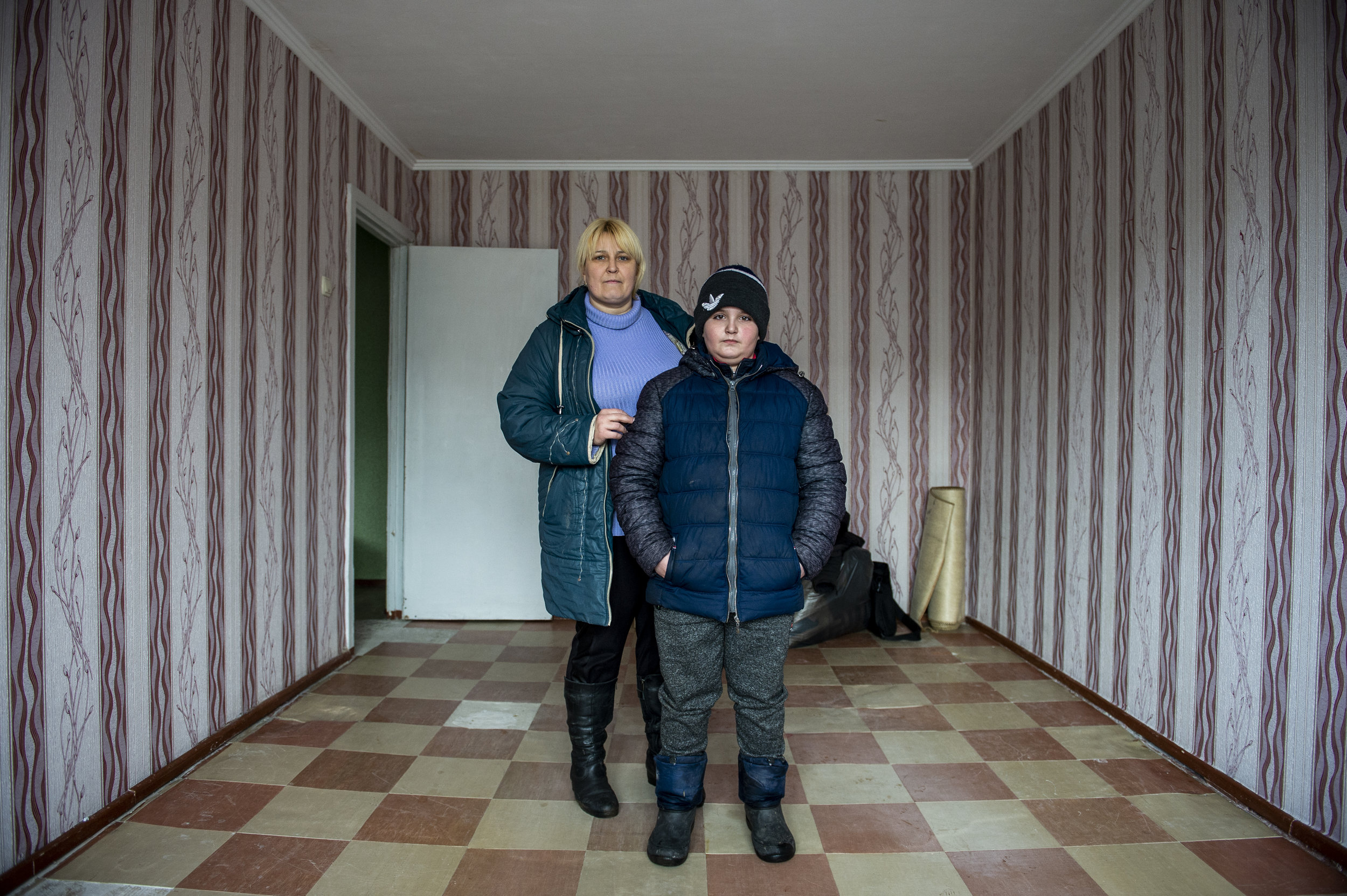 A mother and son who moved from the frontlines of Zolote to a new apartment several kilometers from Point Zero.