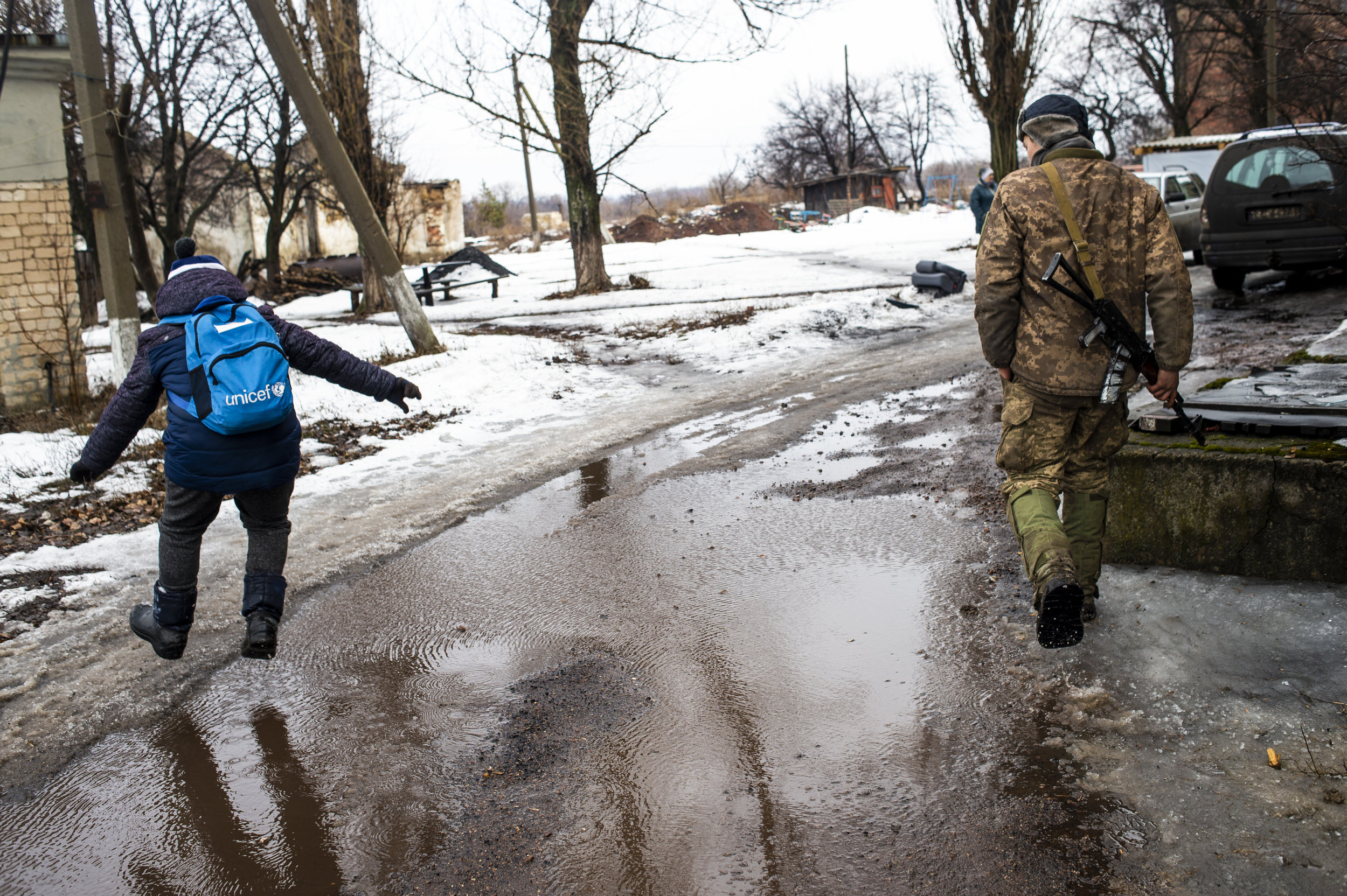 A student returning home from school in Zolote jumps over a puddle as he walks beside a soldier from the 54th Mechanized Rifle Brigade. The young boy lived only a hundred meters from Point Zero and made the walk to and from school alone.