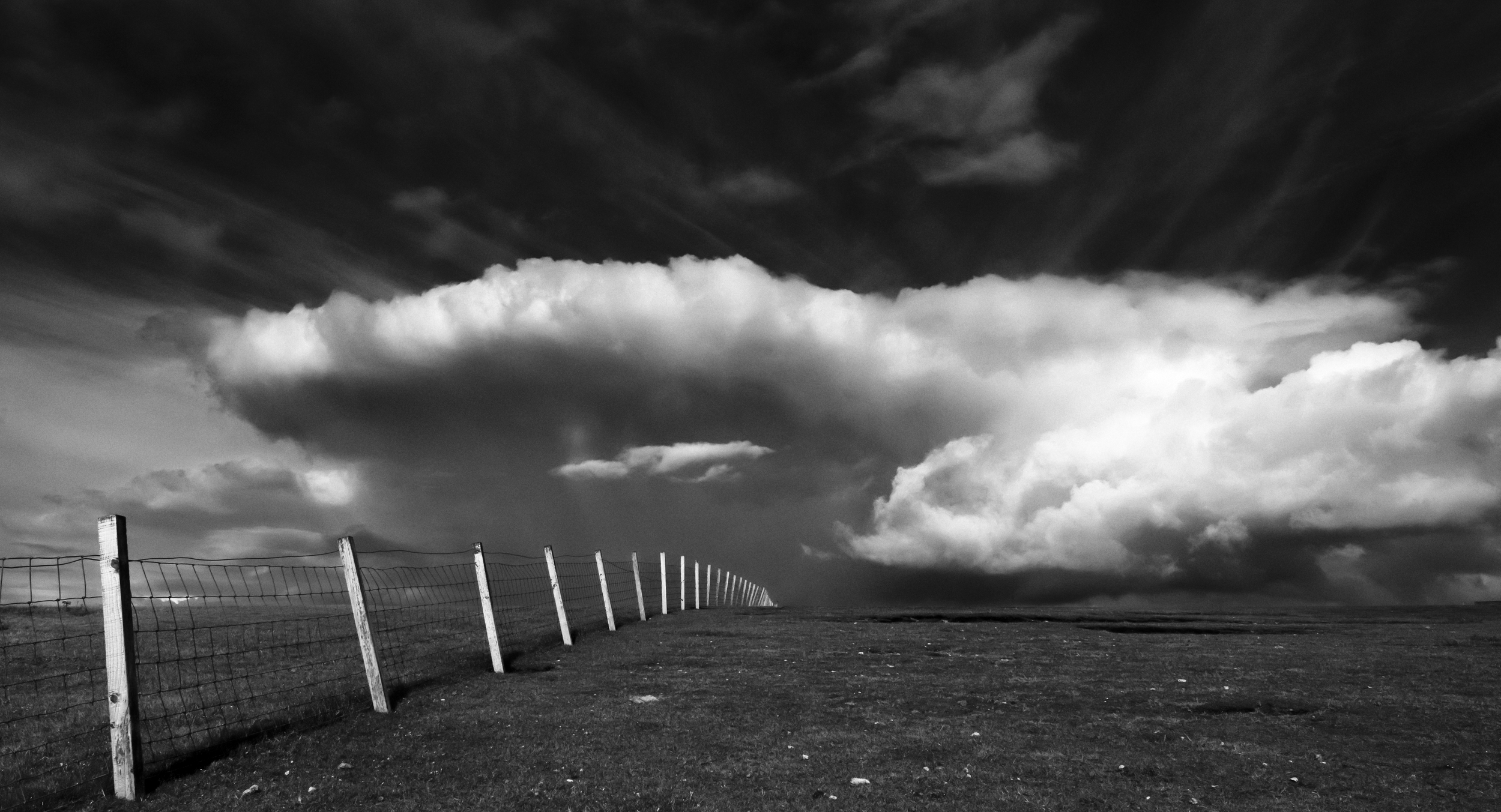 A safety fence curves across the surface of Aird Feinis, Lewis.