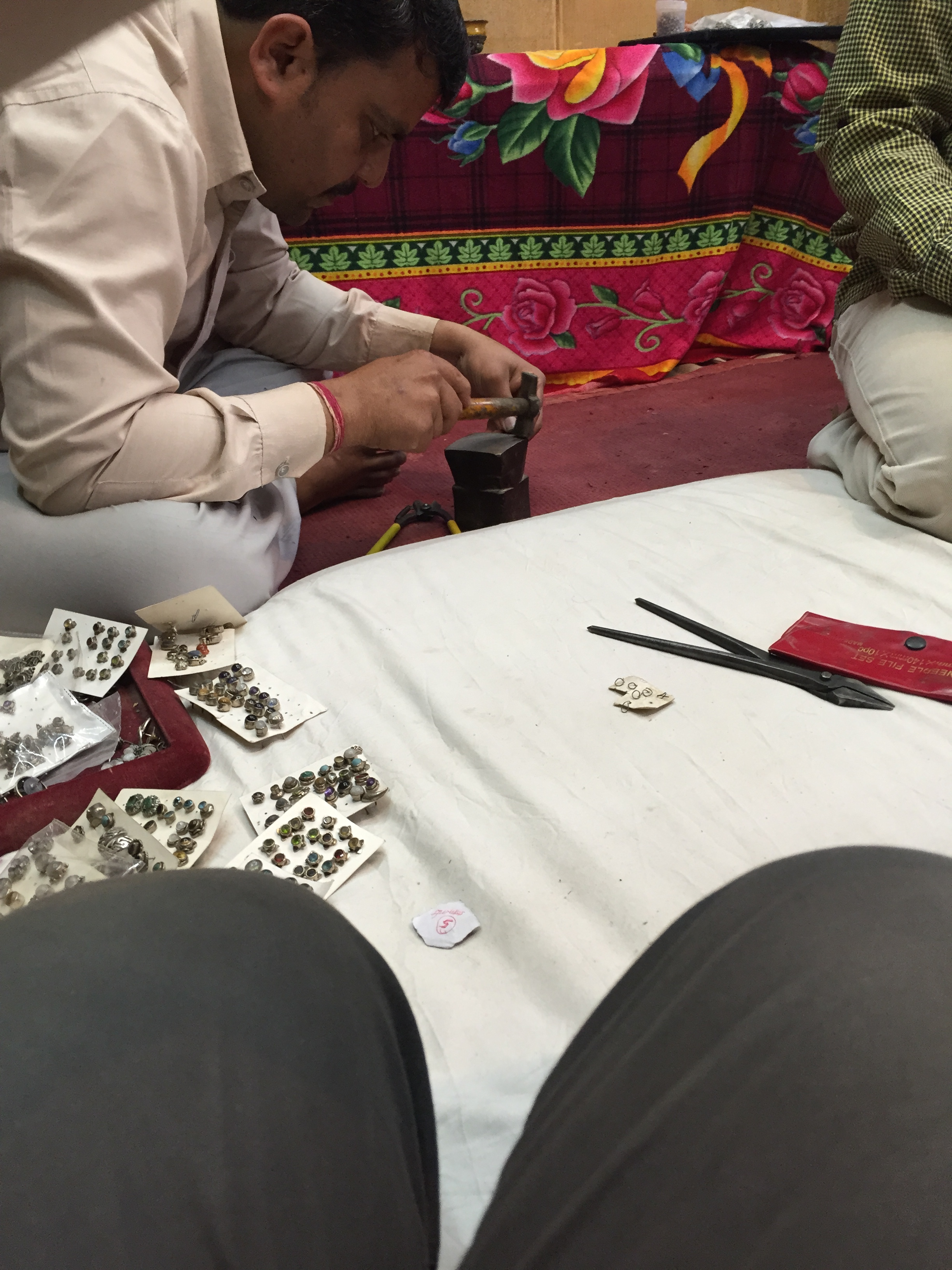 The earrings being hammered and filed to sharpen the ends.