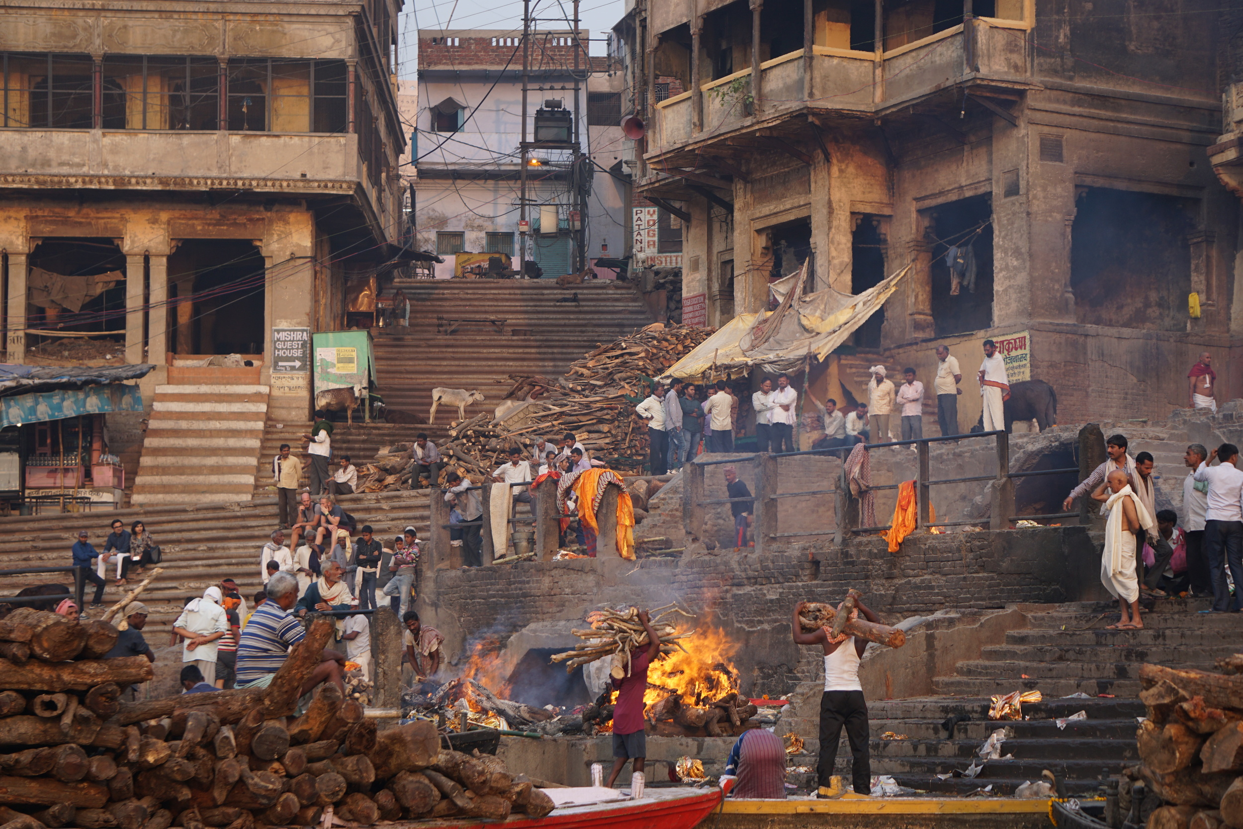 Men carrying logs for more pyres at a burning ghat.