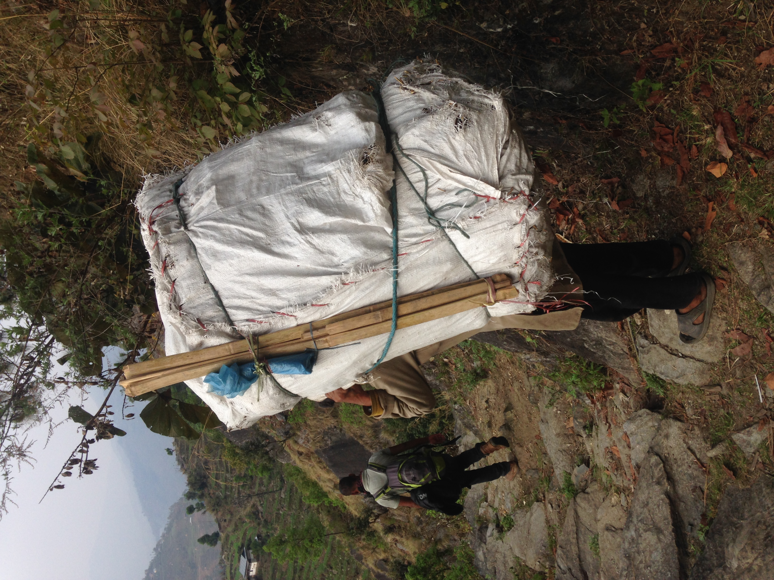 Nepali porters on the trail carrying items larger and often heavier than they are.