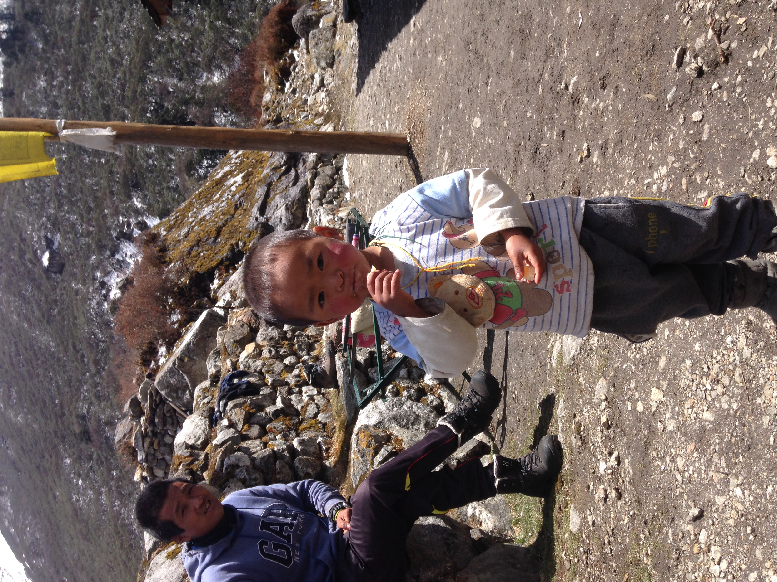 A kid eating yak cheese at our highest teahouse in Cheram.