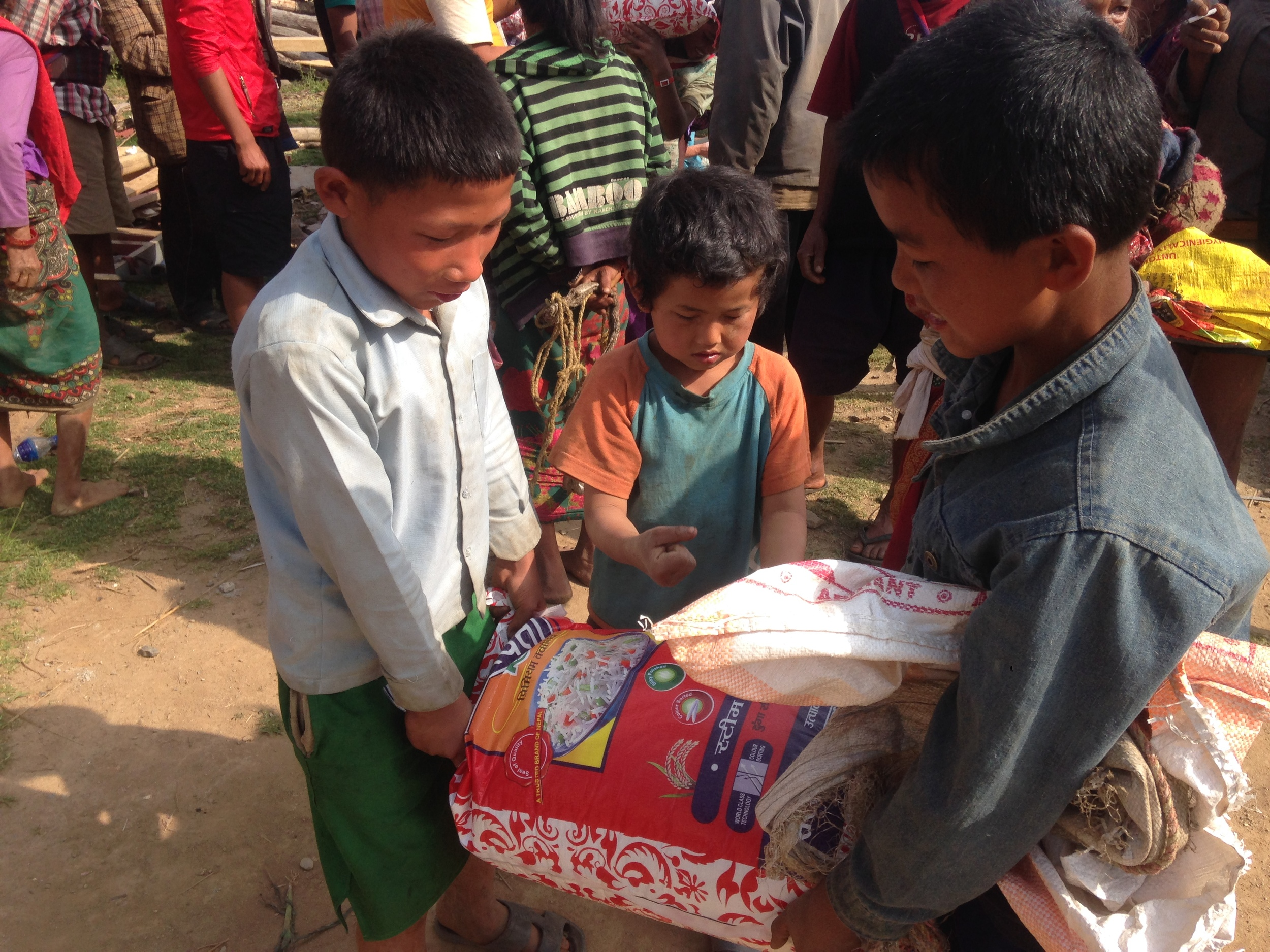 Boys work together to carry rice back to their household.