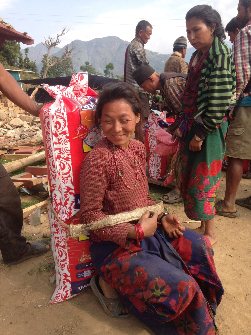 Another woman preparing to shoulder a heavy bag of rice.