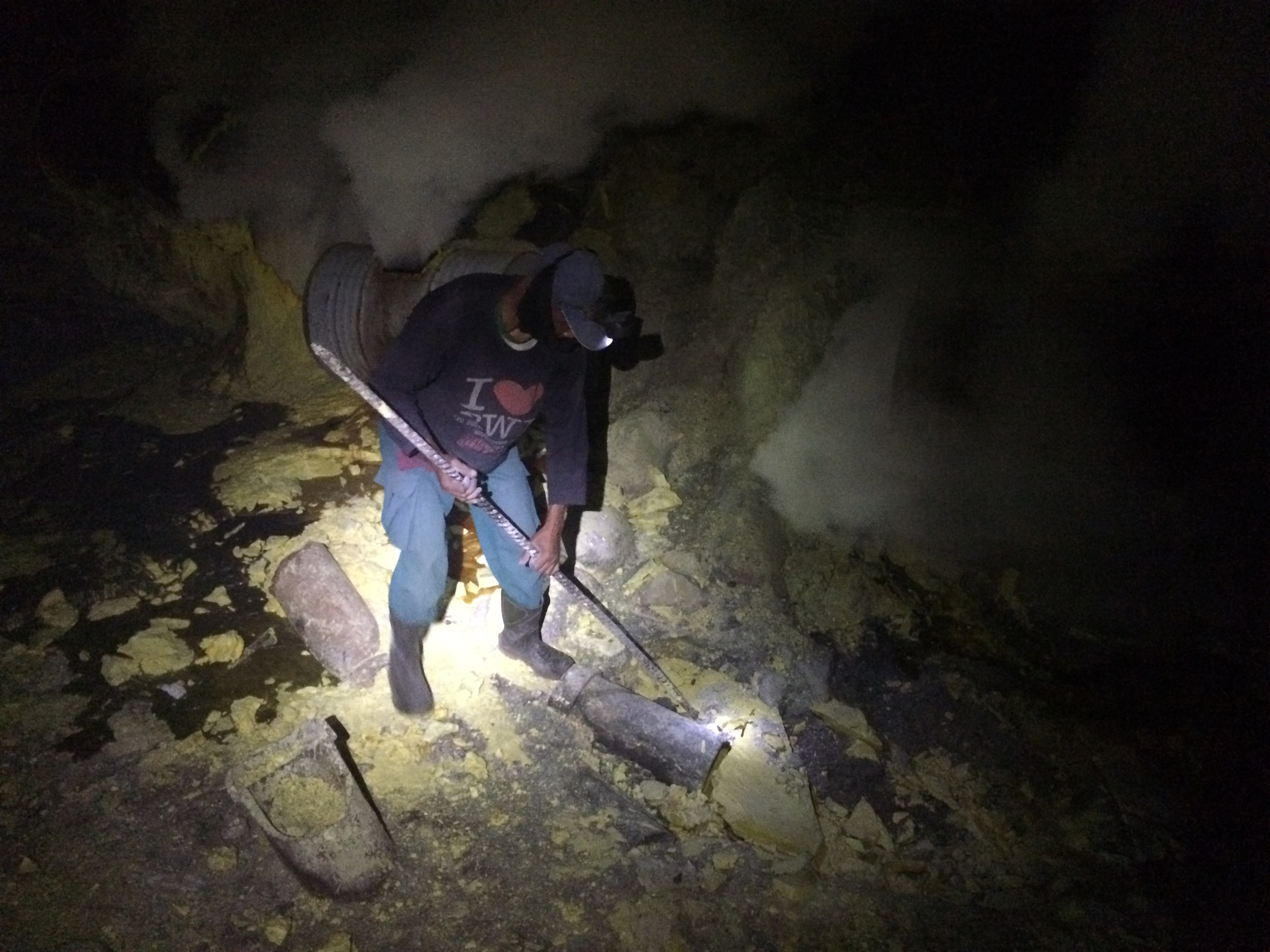 Miner chipping away pieces of sulfur