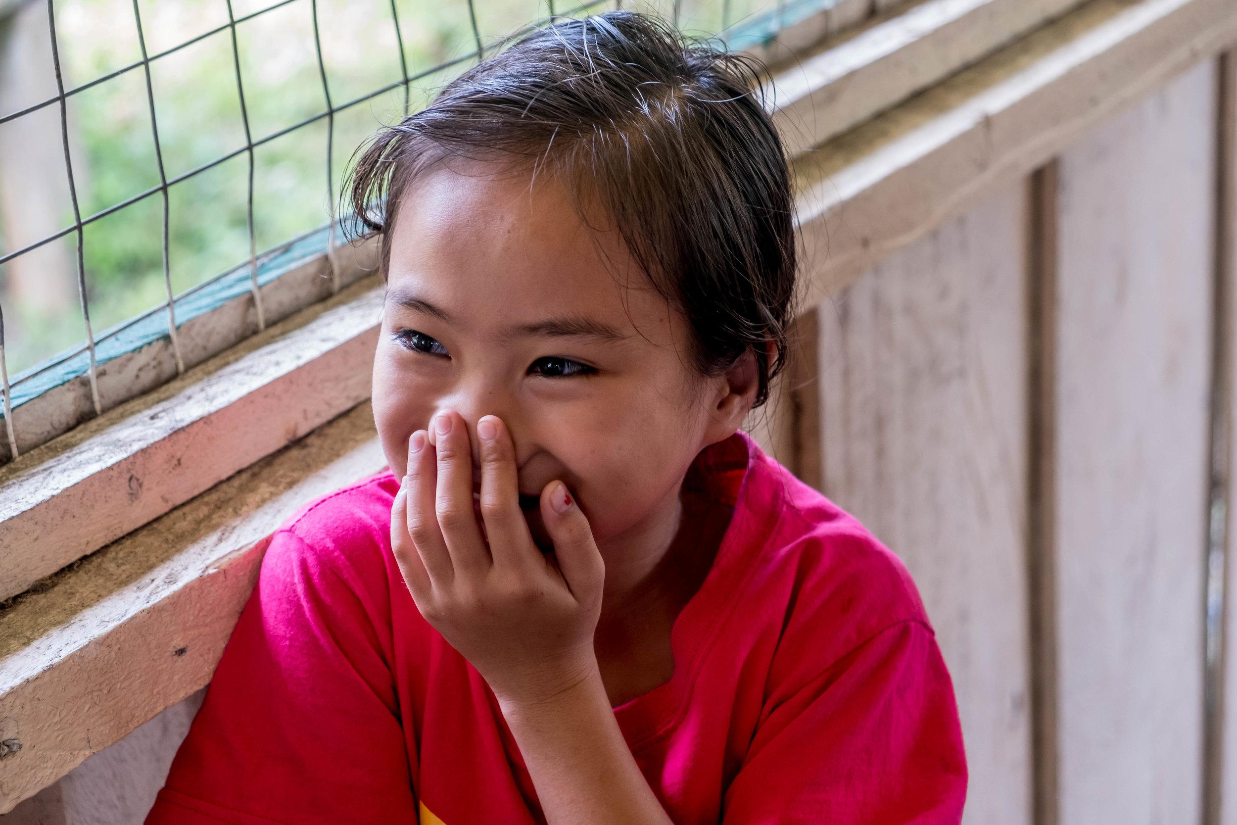 Little girl hiding her smile
