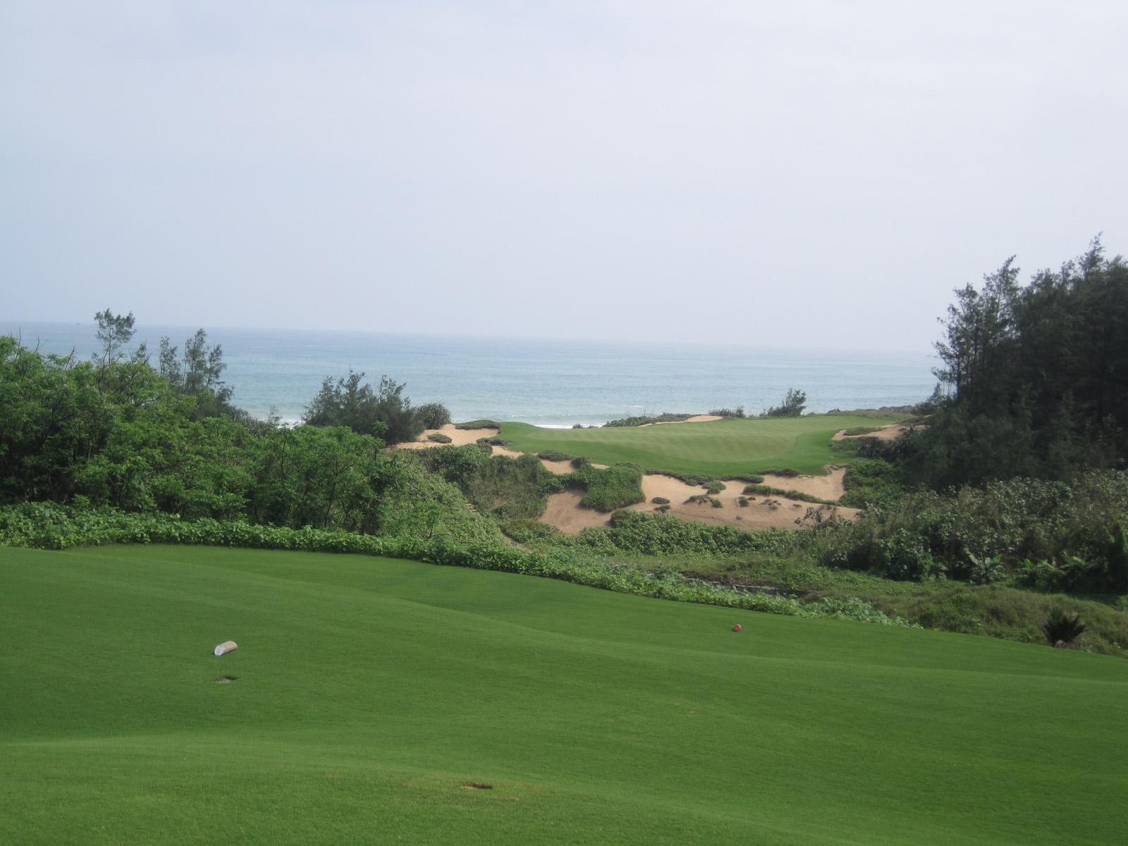 The short, 150 yard 8th hole at Shanqin Bay, South China Sea in the backdrop