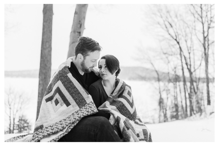 lake dunmore vermont winter engagement portrait session wrapped in a quilt