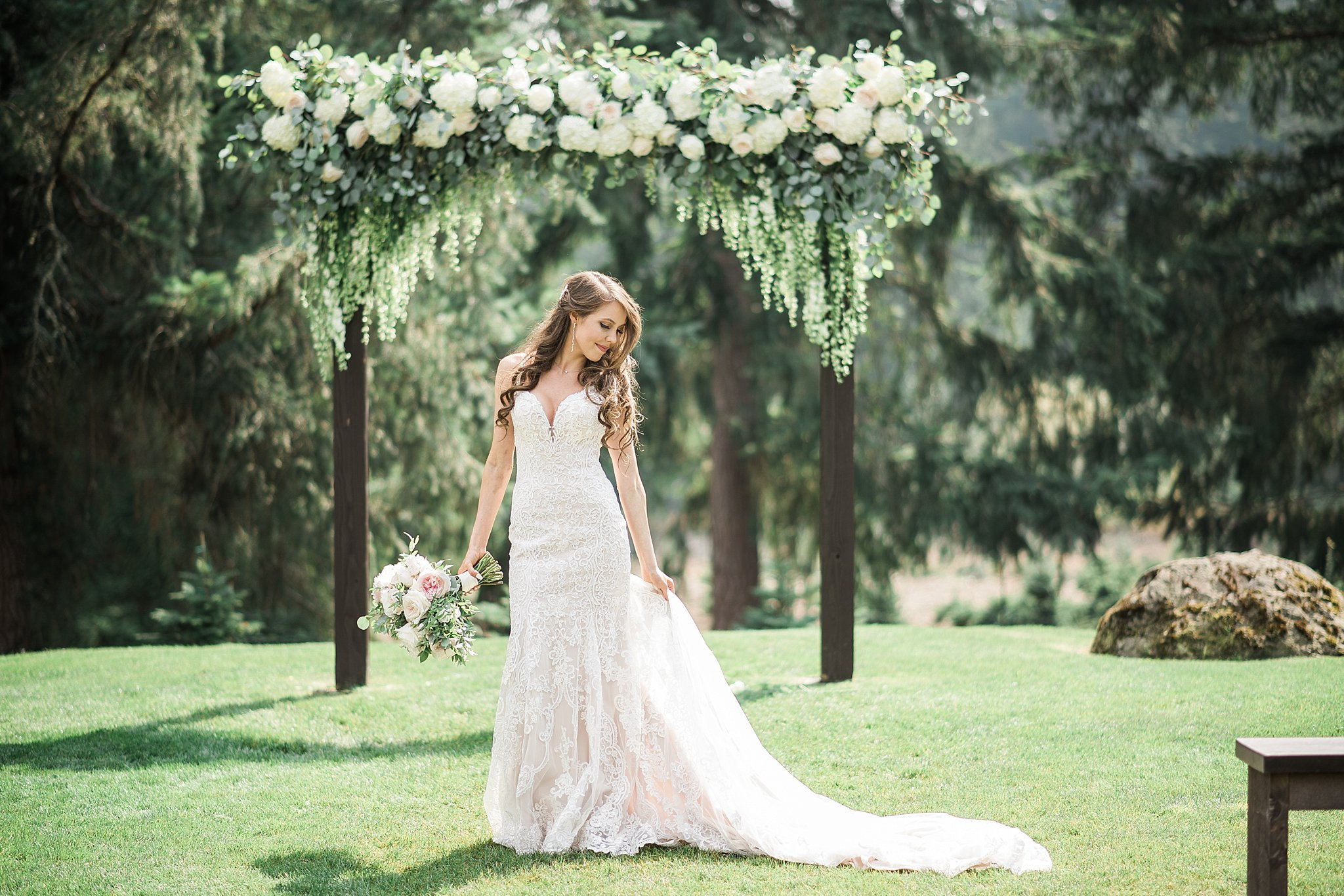 The bride in front a gorgeous white & green floral arch by Bloom