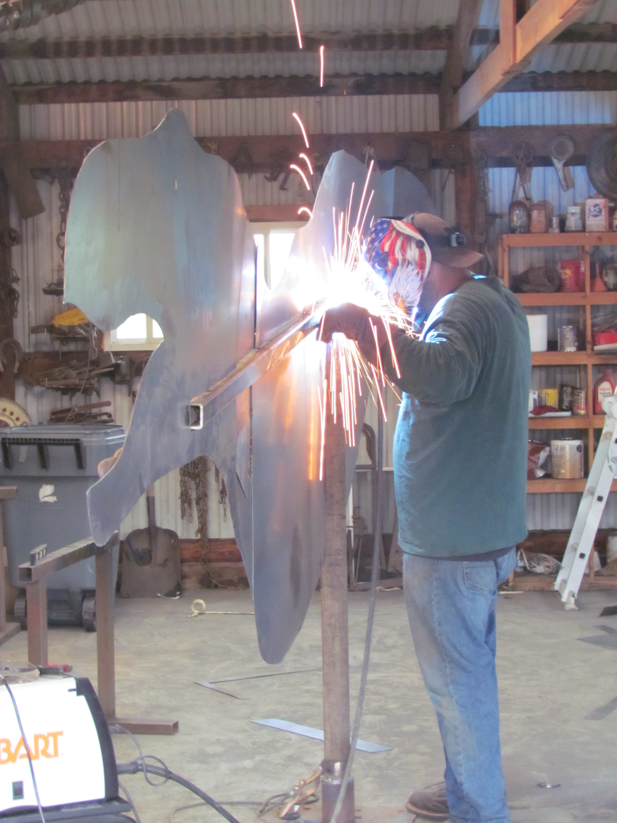 Apprentice Shaun Re welding on a the frame for a new T-Rex scrap iron sculpture.  Photo by Teri McTighe.