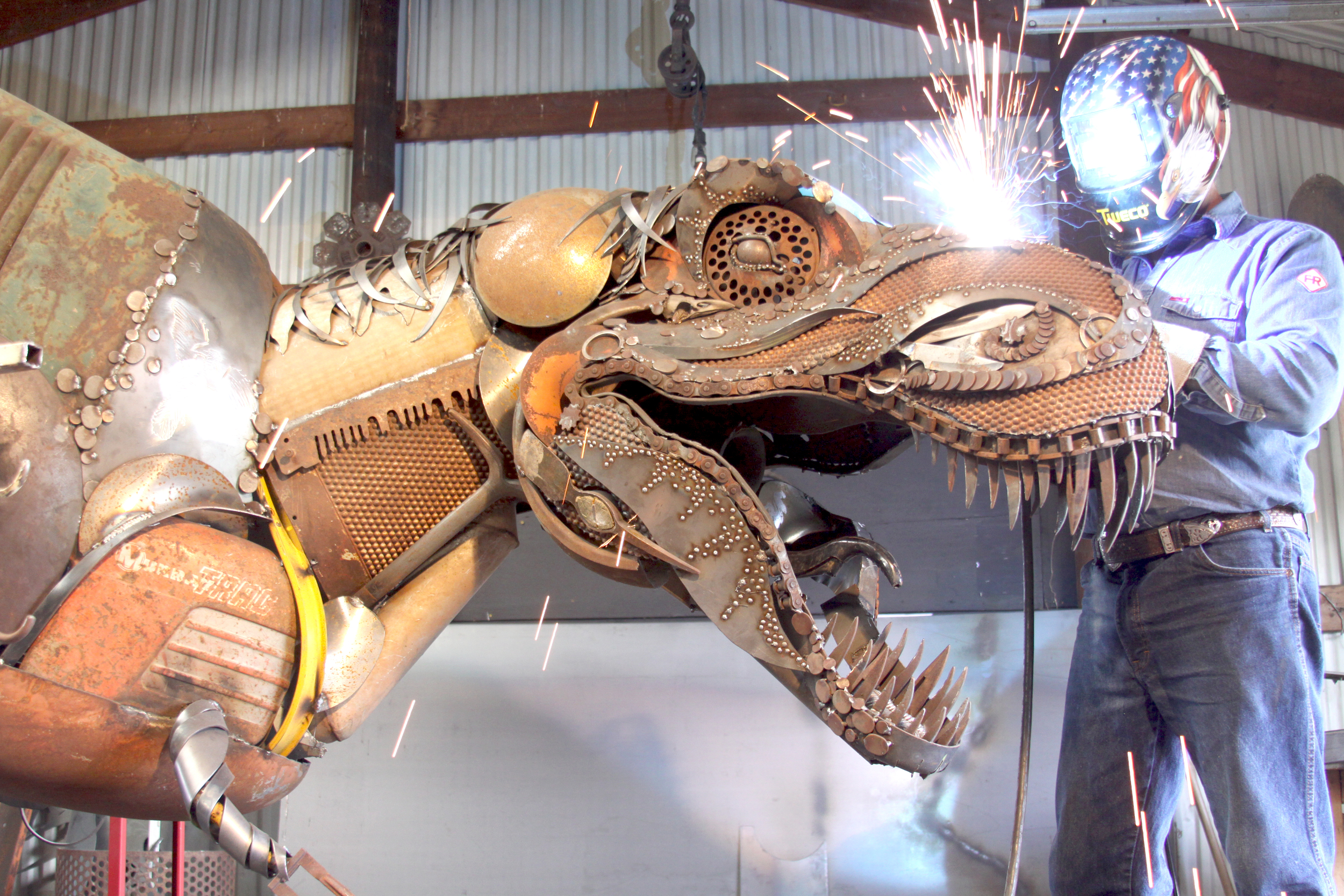 Sparks fly in the shop during the construction of a 13 foot long T-Rex.