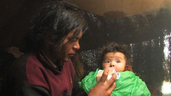 Locho gives Jiatomah her bottle of yak milk